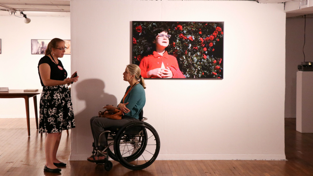 two people talking in wheel chair accessible art gallery