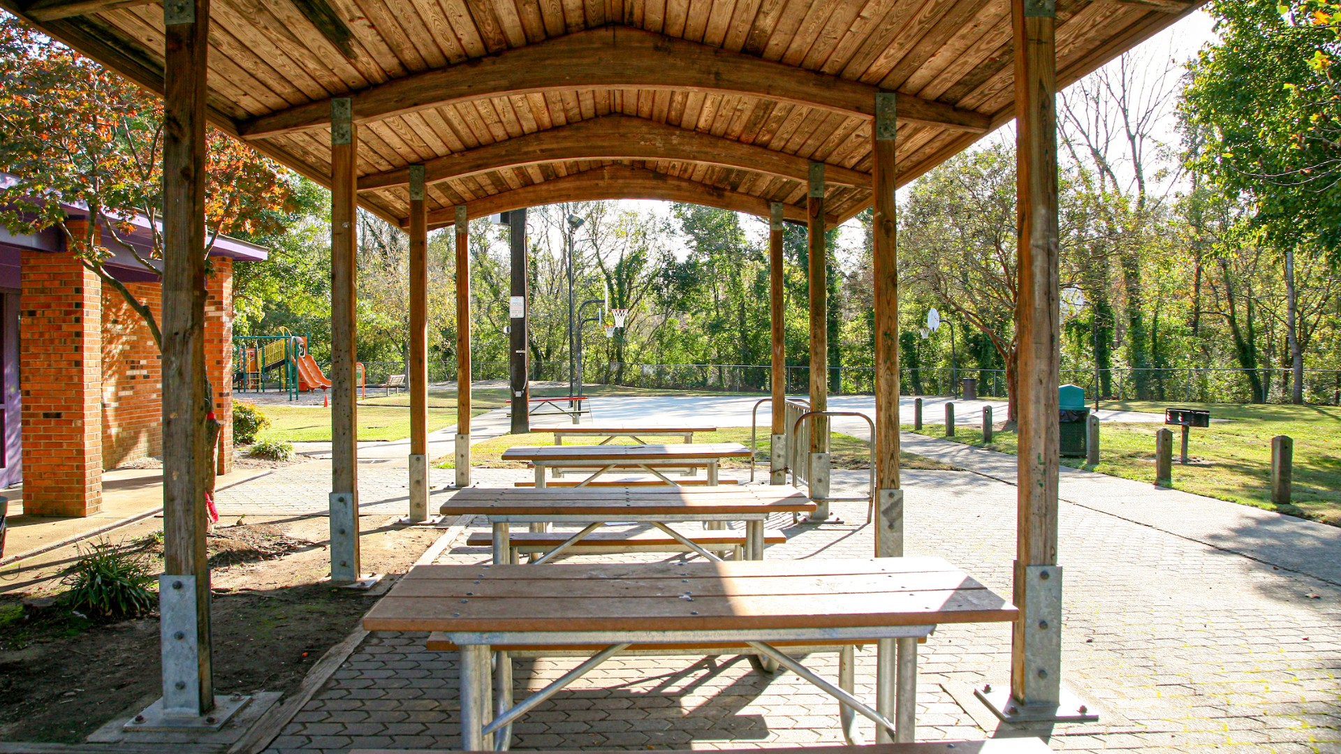 Wooden picnic shelter with view of basketball courts in the background at Apollo Heights Park