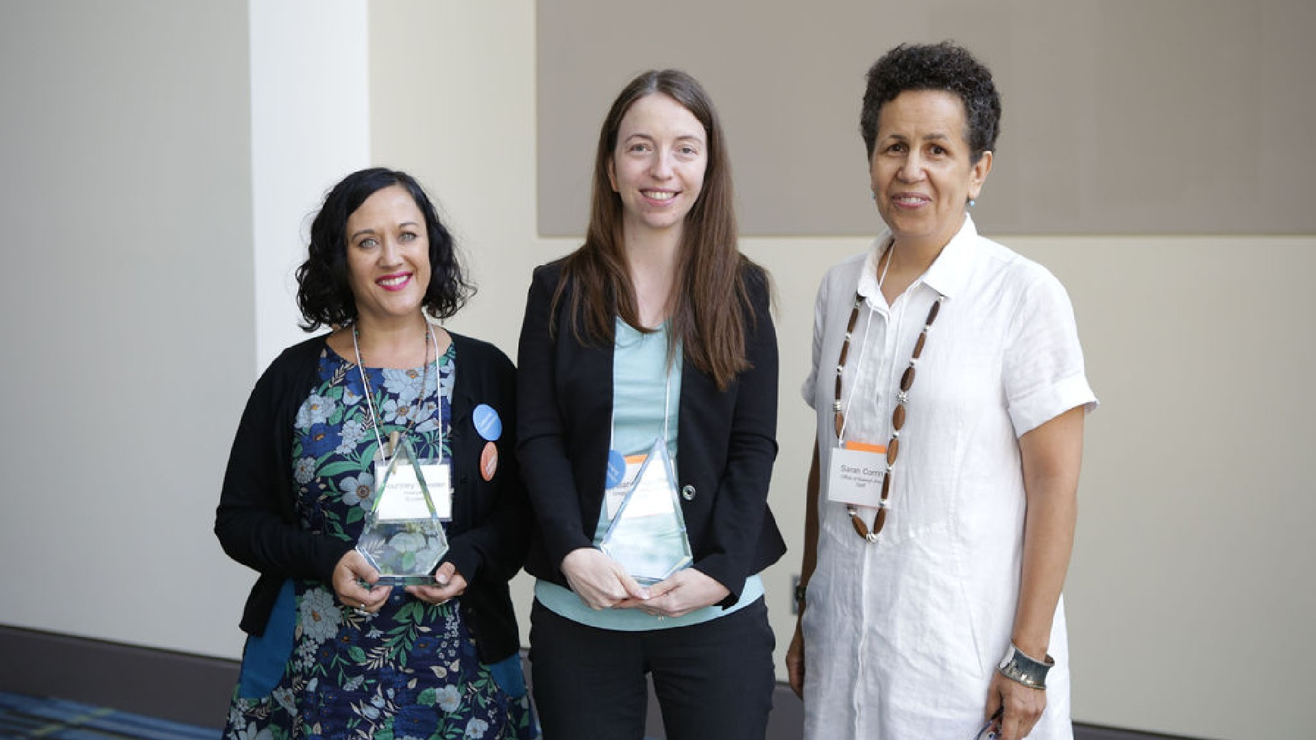 three women smiling, two of them are holding glass awards