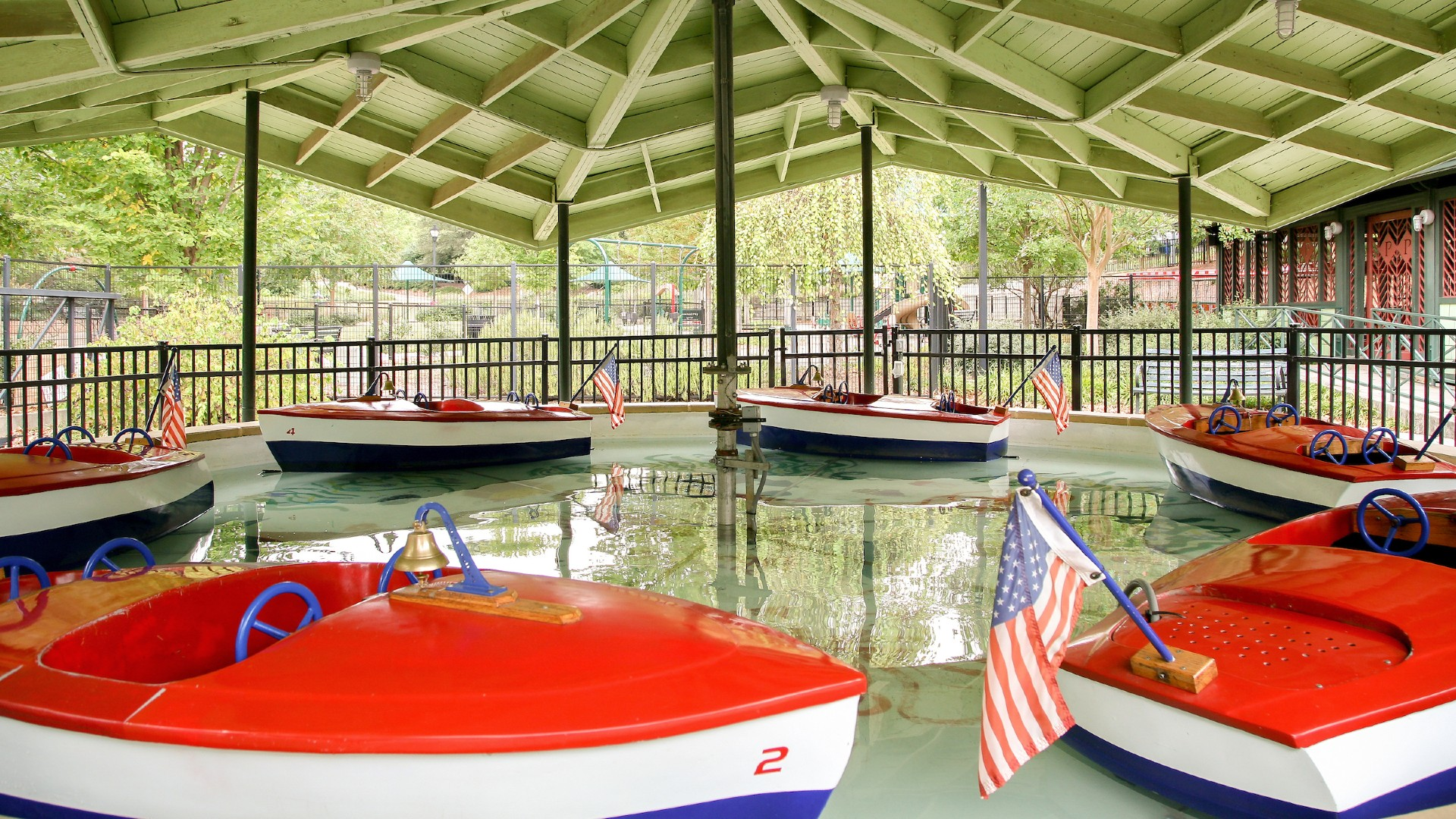 view of six empty kiddie boats floating under the pavilion at pullen park