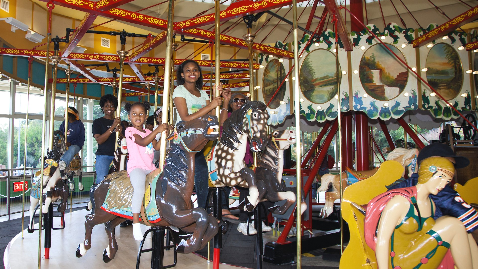 Family with two girls smiling on the carousel horses at chavis park