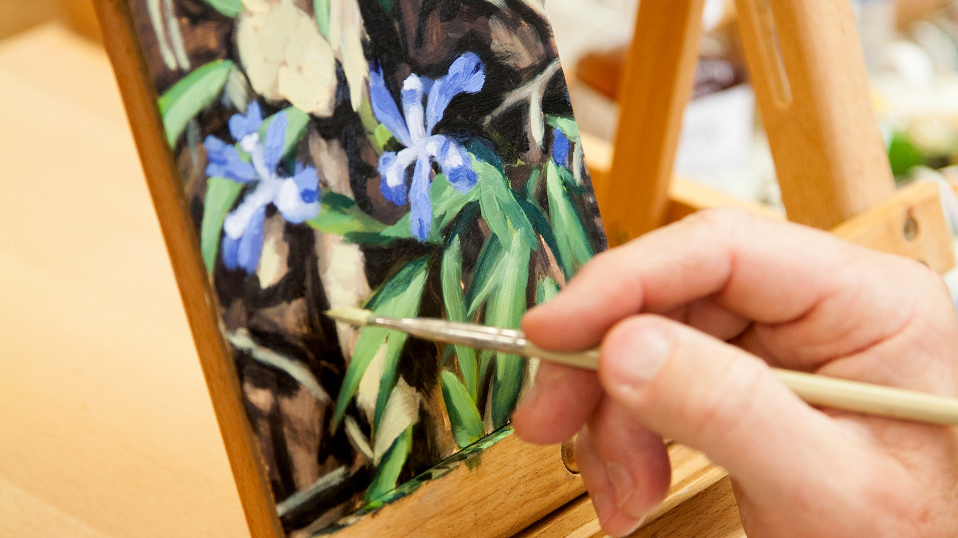 hand with a paintbrush working on a flower painting