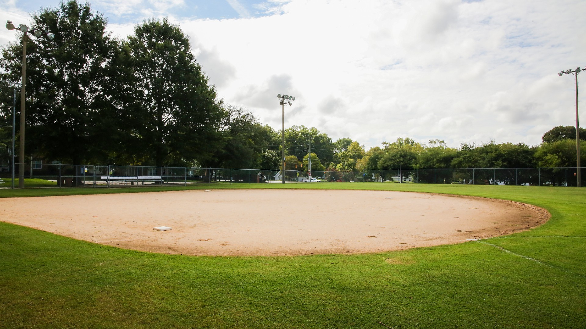dirt baseball field surround by grass outfield and lights at chavis park