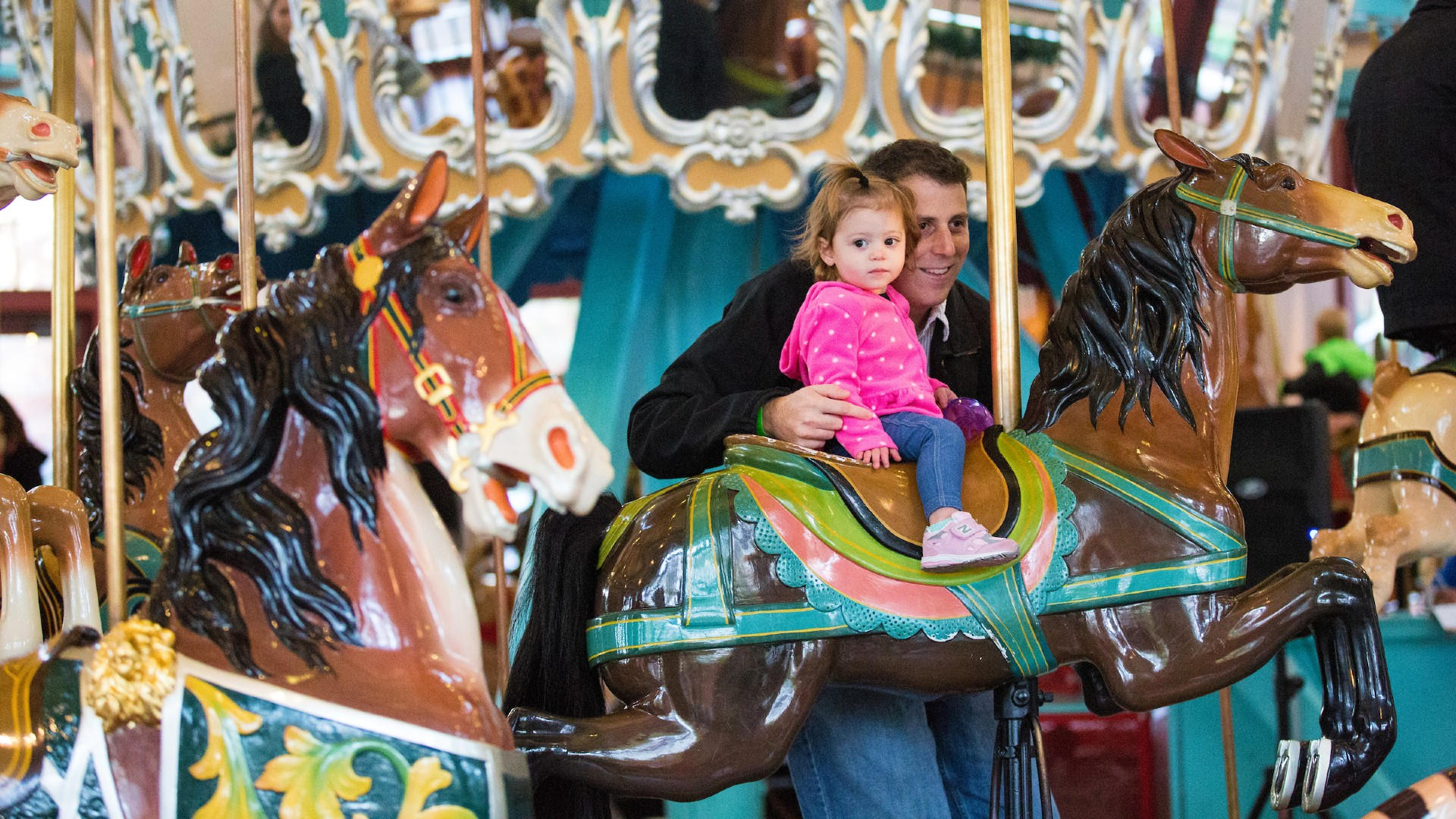 Toddler girl riding a pony on the carousel at Pullen Park
