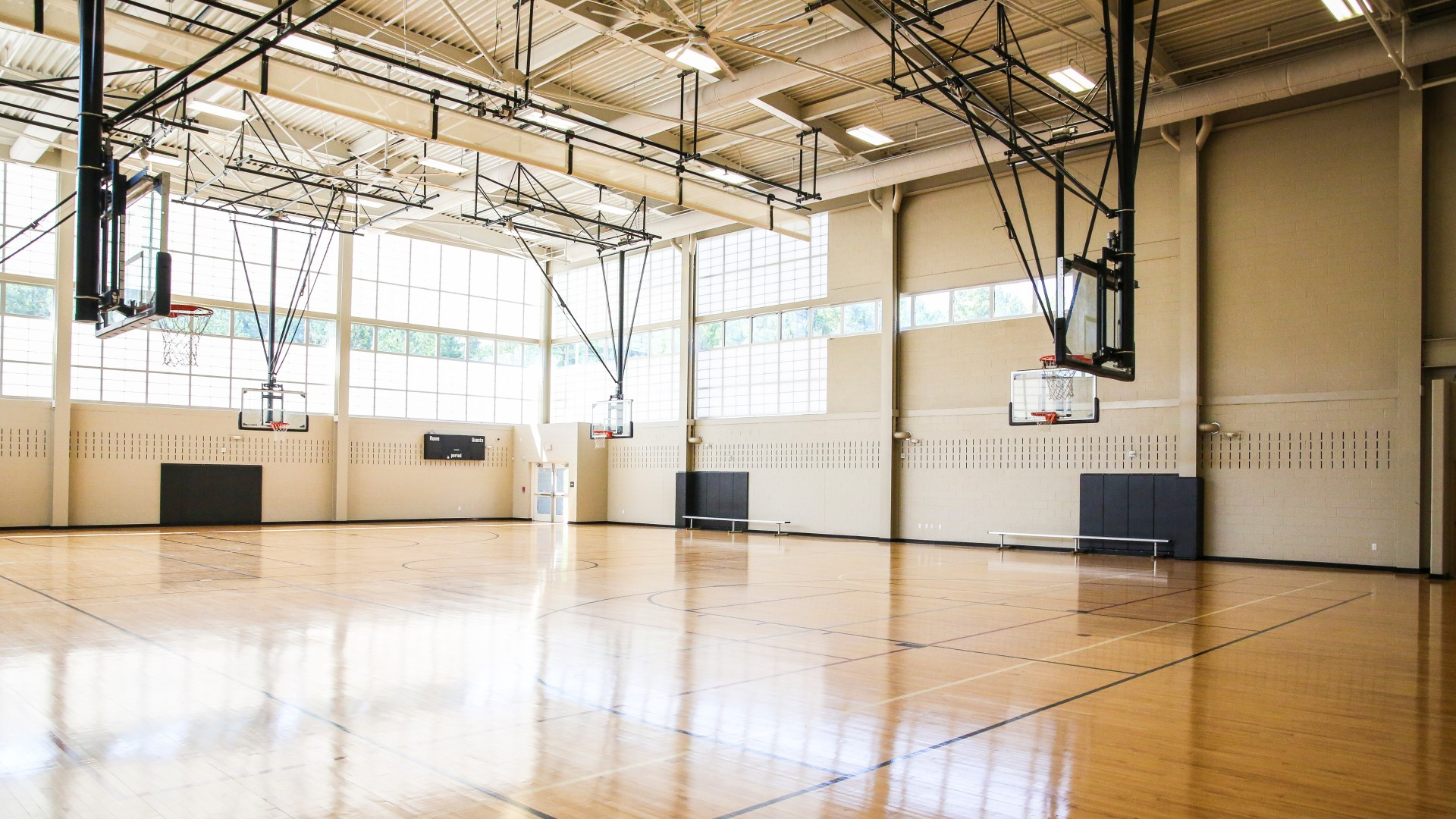 Indoor gymnasium at Abbotts Creek Park with several basketball courts and hoops.
