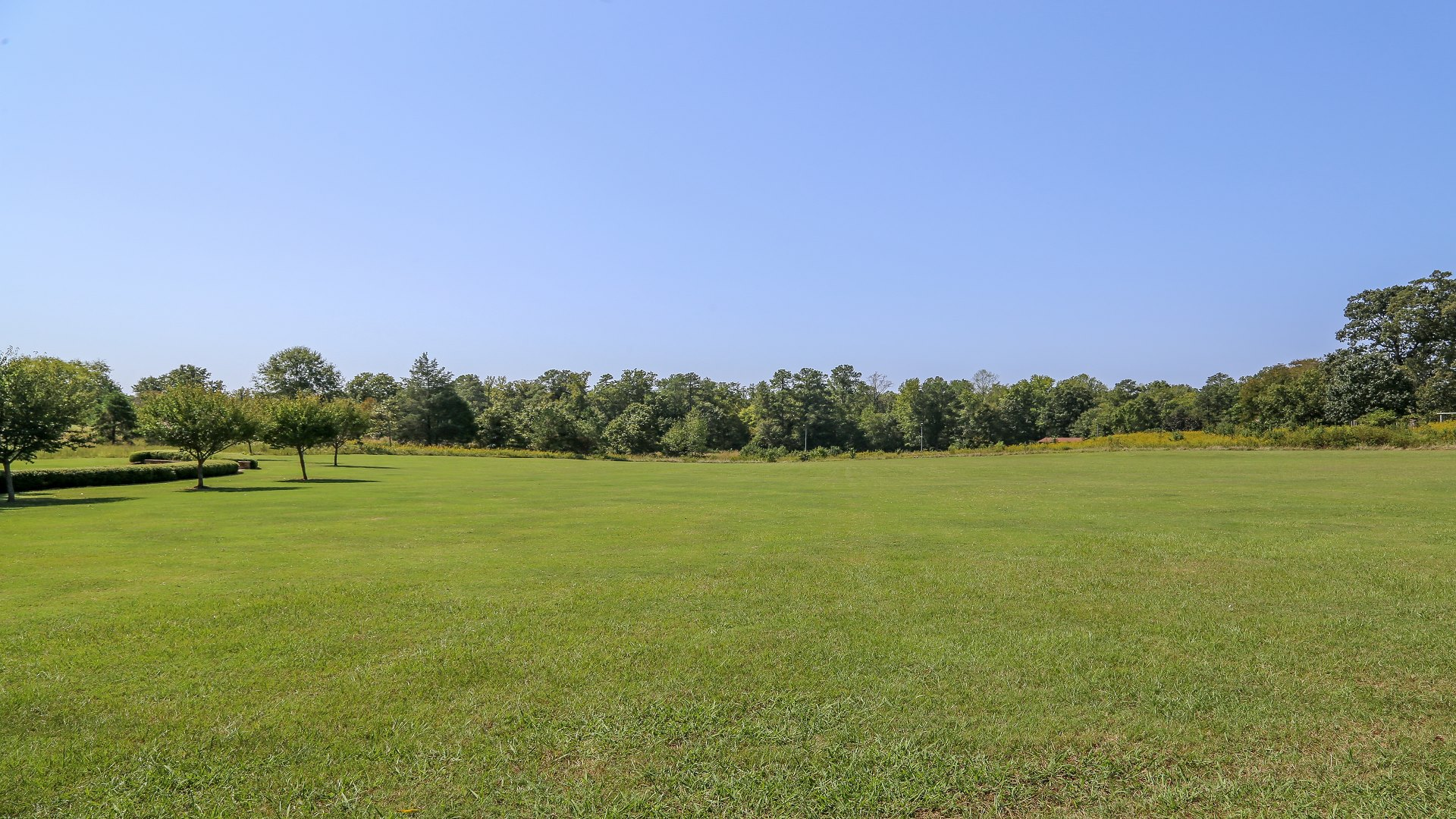 A large open field located near the large picnic shelter
