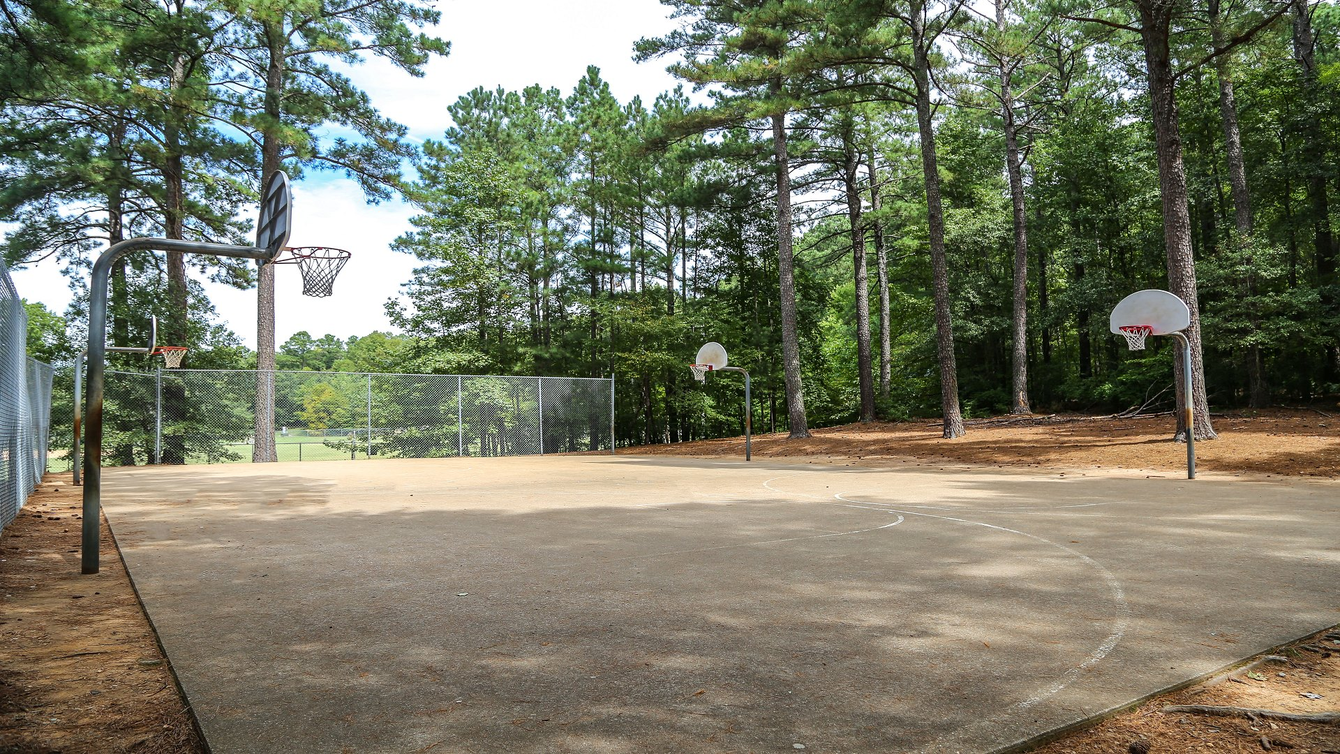 Concrete outdoor basketball court with four hoops at Biltmore Hills