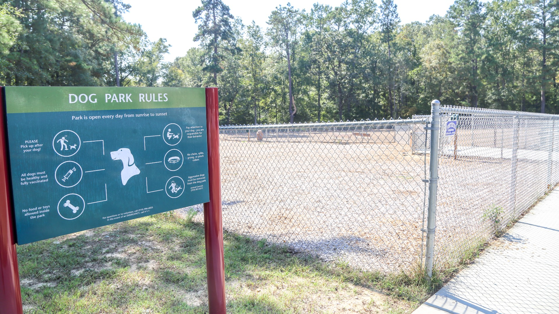 An outdoor, fenced in dog park at Buffaloe Road next to a sign with dog park rules