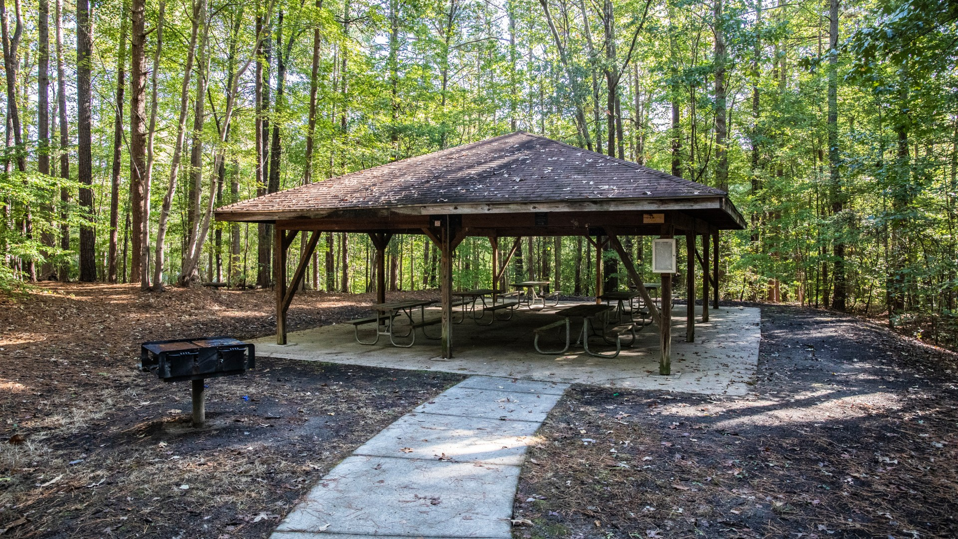 Outdoor picnic shelter at Cedar Hills Park featuring six tables and a grill