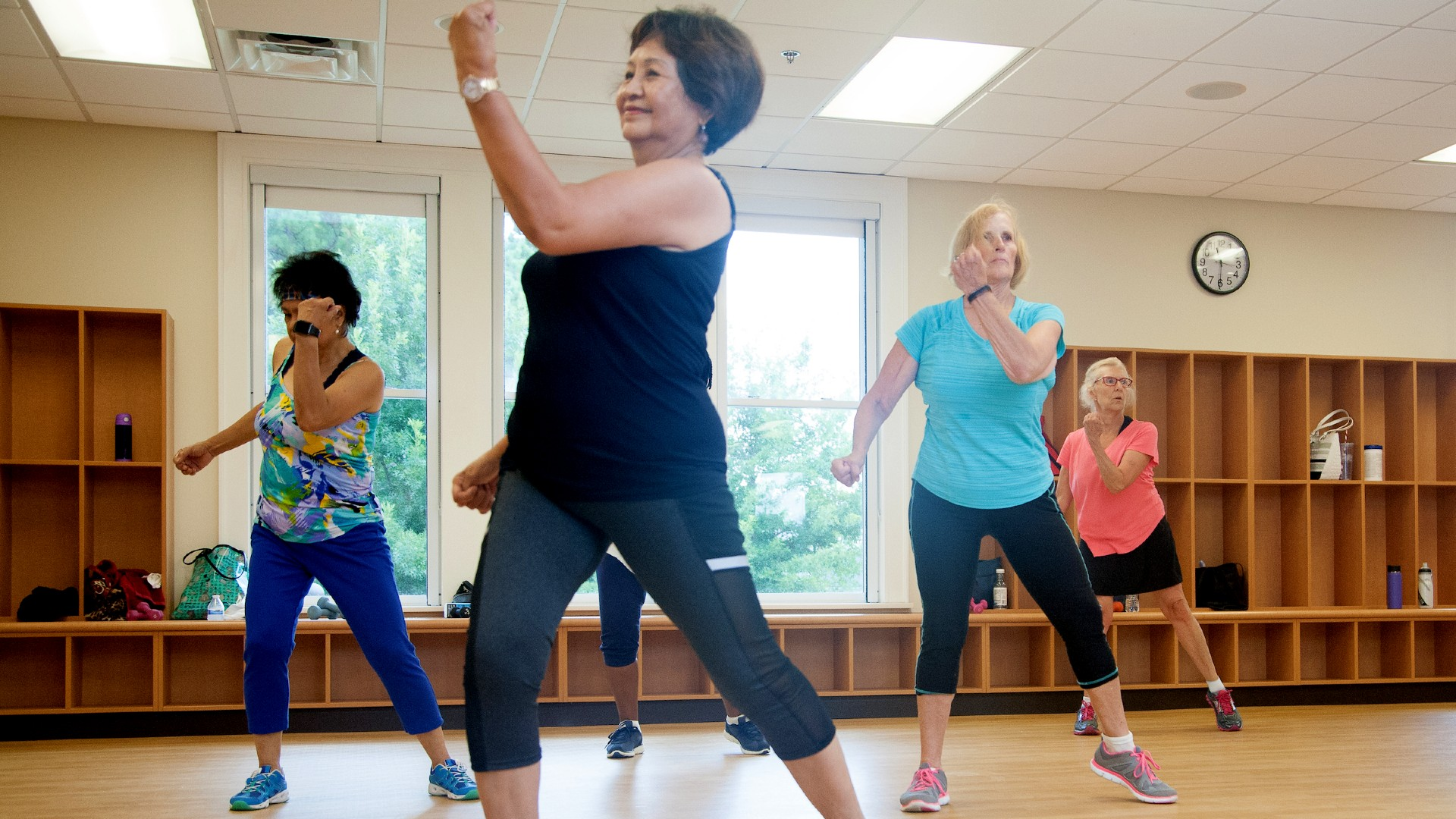 Woman smiling leading a cardio fitness class for women at Millbrook Community Center.