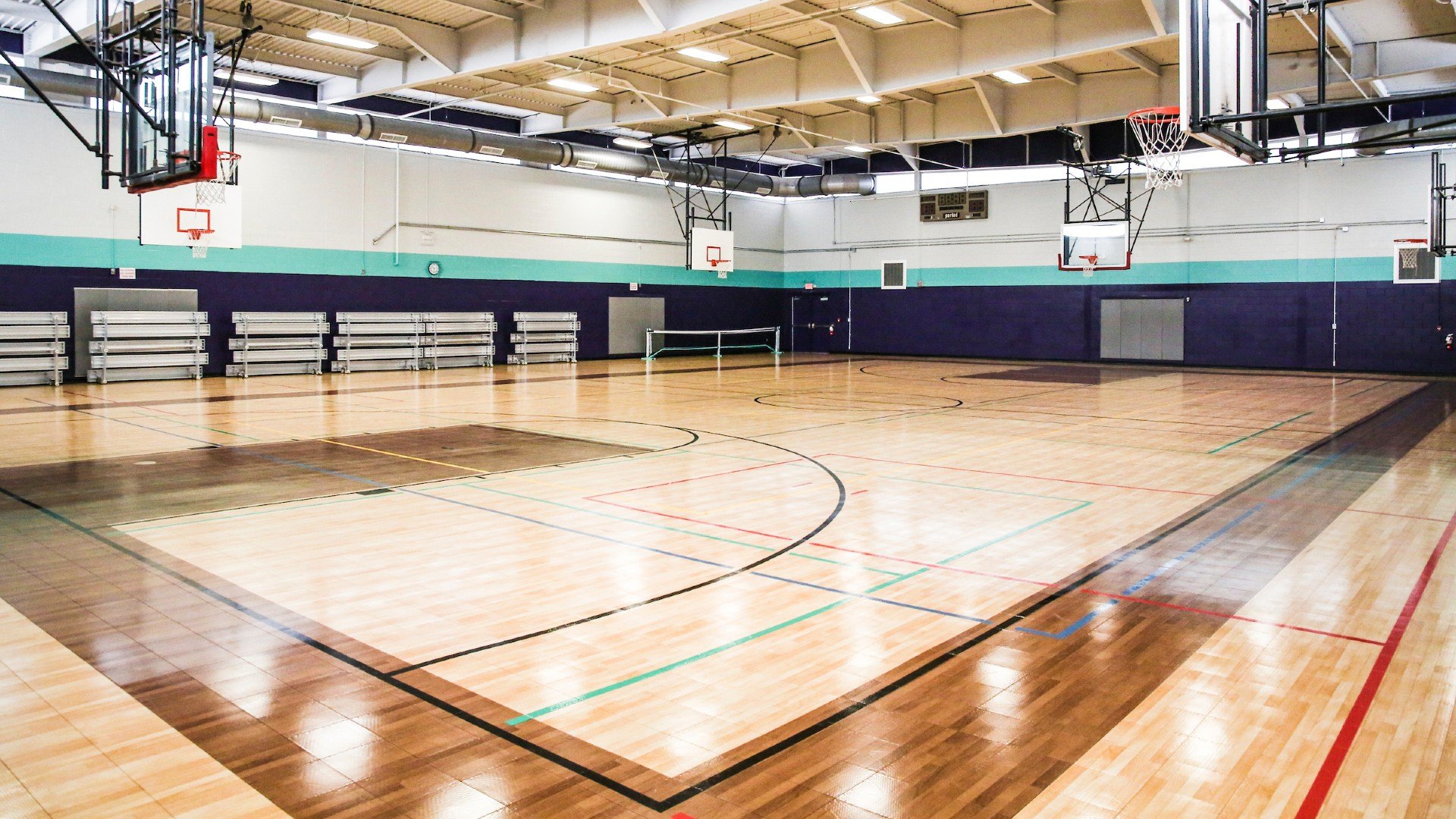 empty gymnasium at Millbrook Exchange commuity center with four hoops