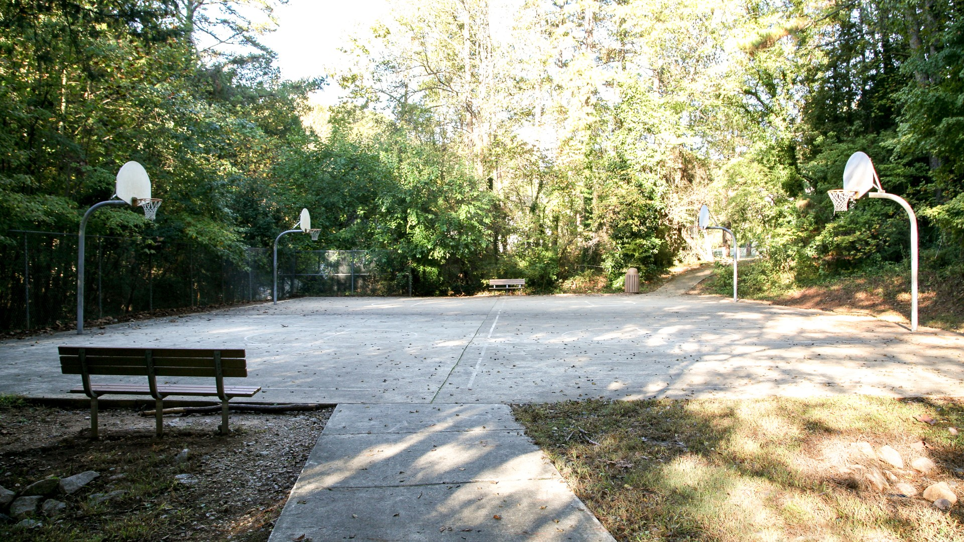 Outdoor basketball court with multiple hoops at Glen Eden Pilot Park