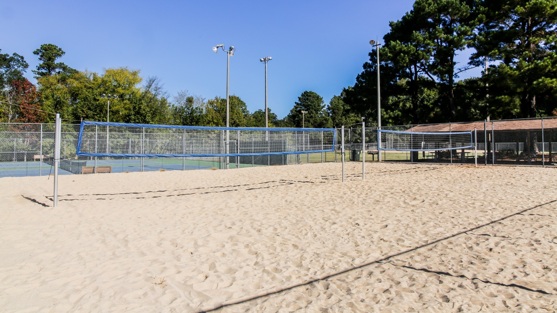 Two of the outdoor sand volleyball courts with lightning at Green Road Park