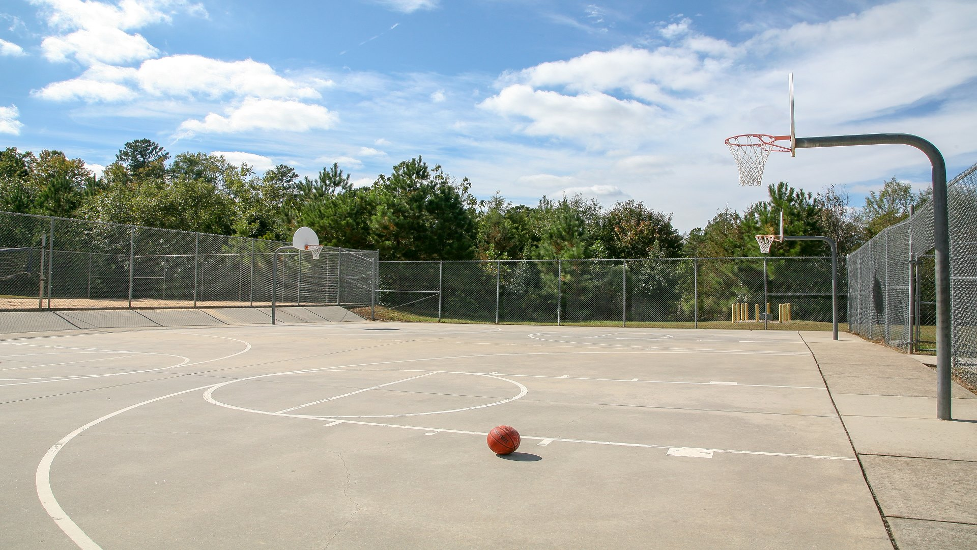 Outdoor basketball court with two hoops at Honeycutt Park