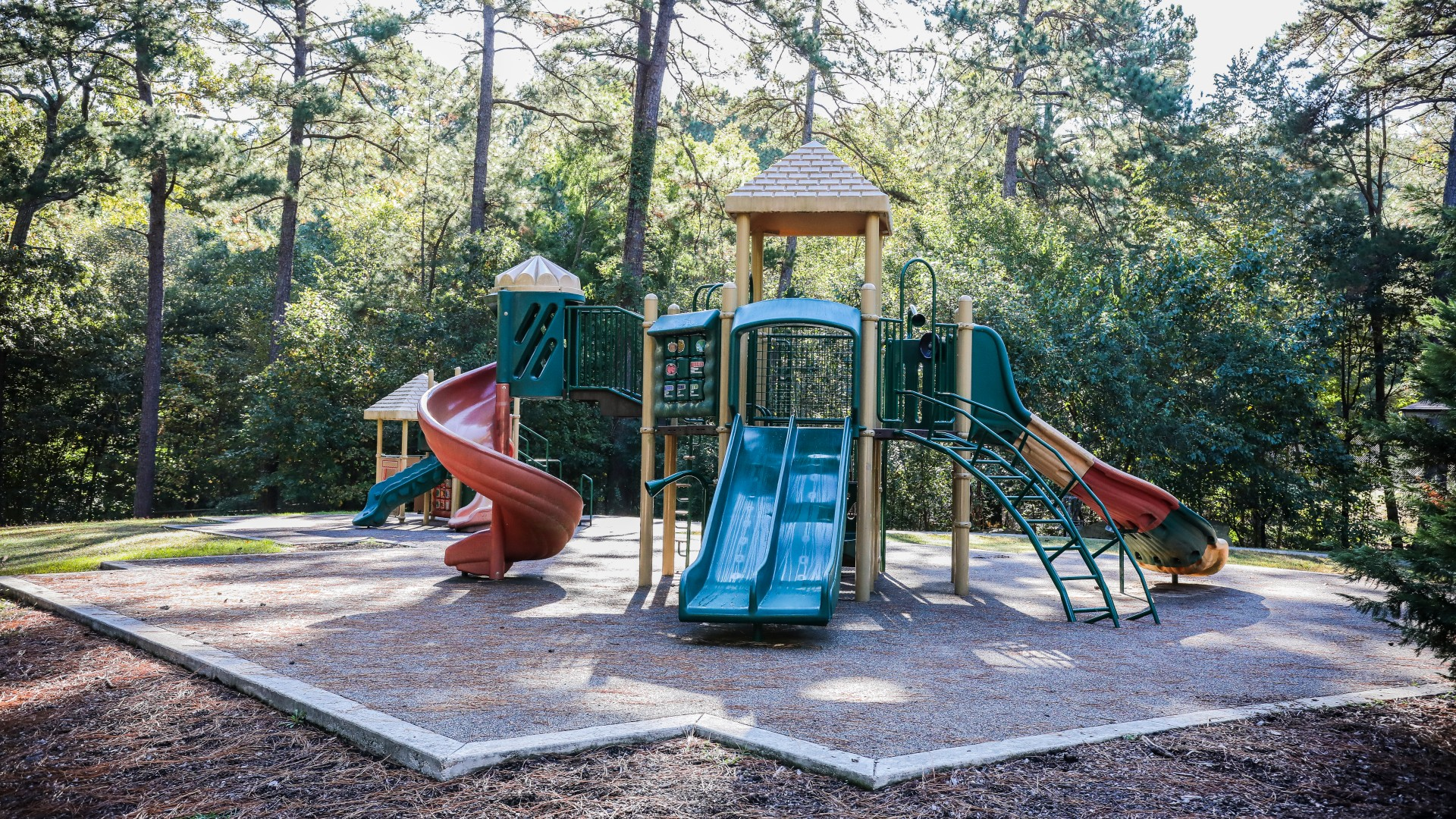 A second playground at Kentwood Park featuring two slides and a rubber surface
