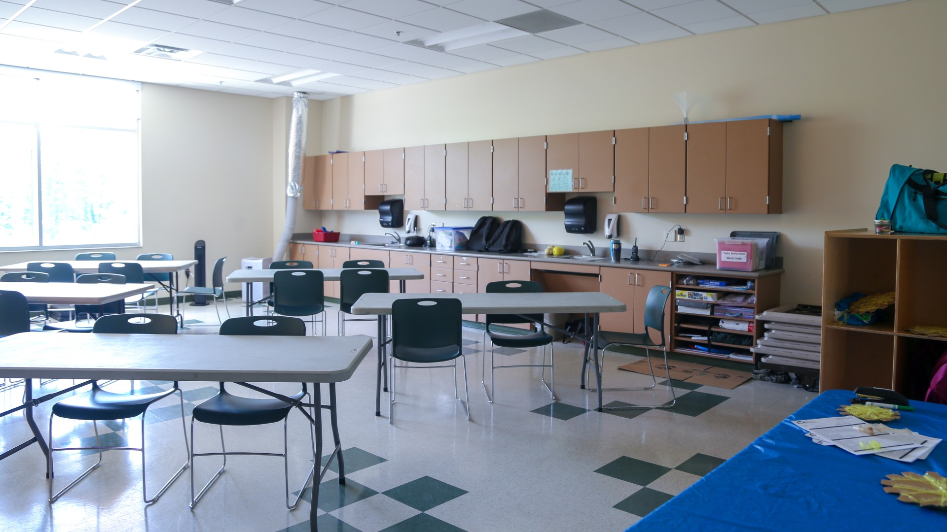 A medium size classroom with tables, chairs, a white board and two sinks at Marsh Creek