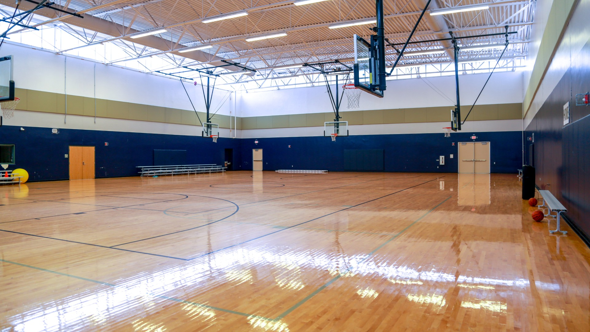 An open gymnasium with multiple courts and basketball hoops