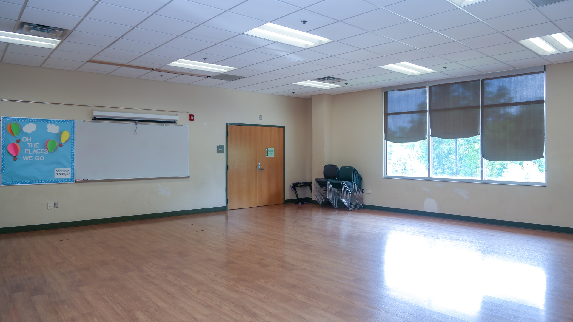 A large open multi-purpose room with a bulletin board and white board