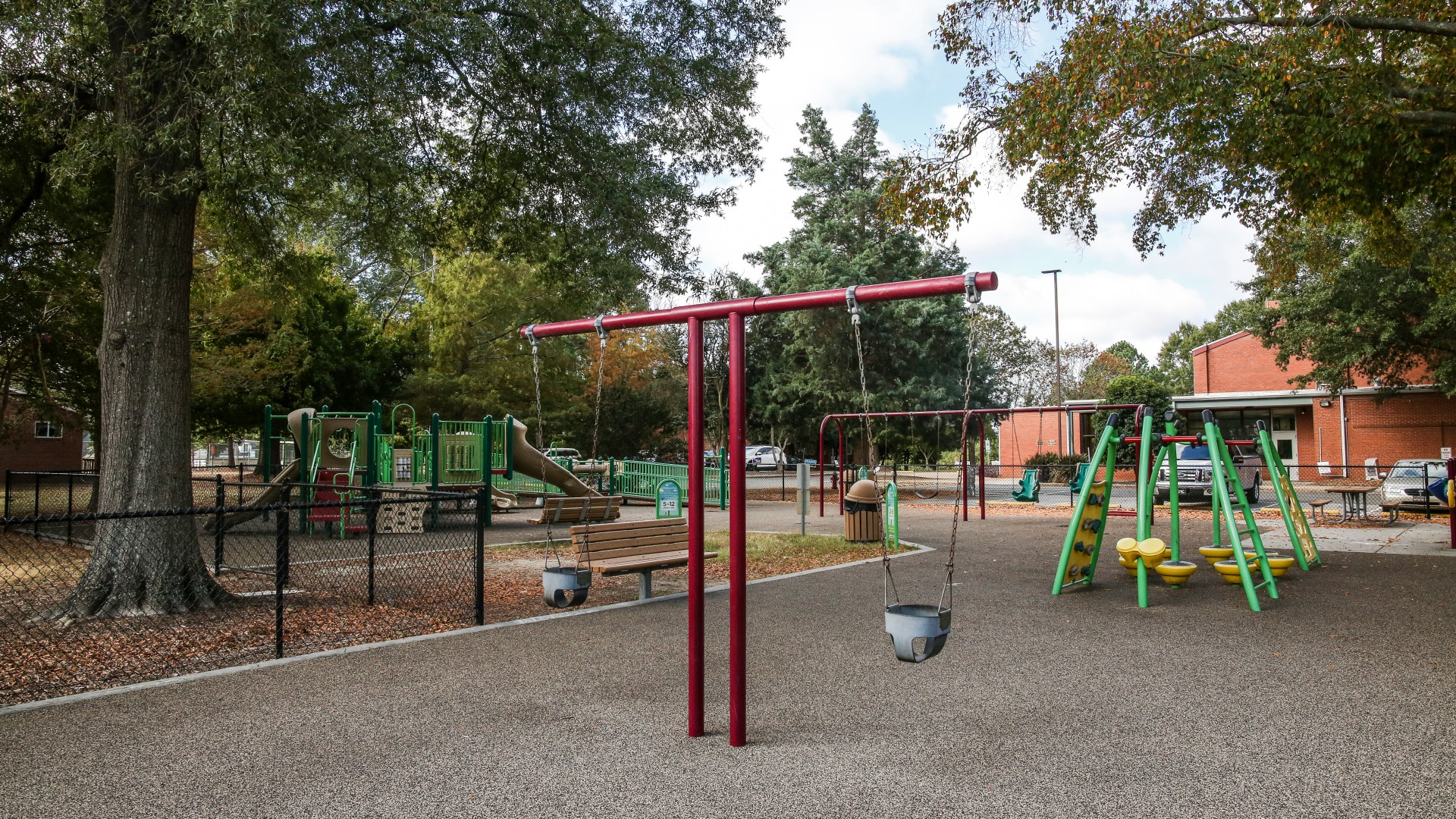 A playground at Method Road Park with swings, slides, climbing equipment and more
