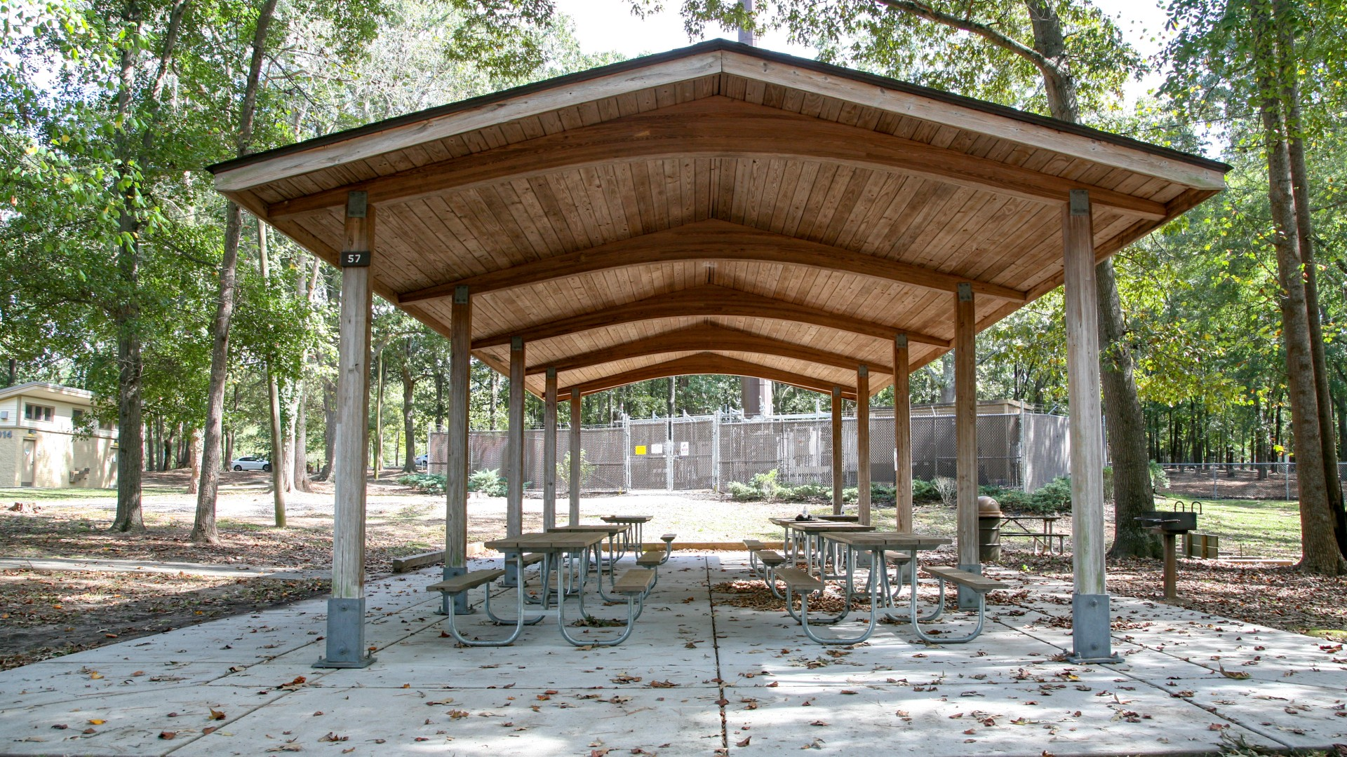 Outdoor picnic shelter with several tables and a grill at Oakwood Park