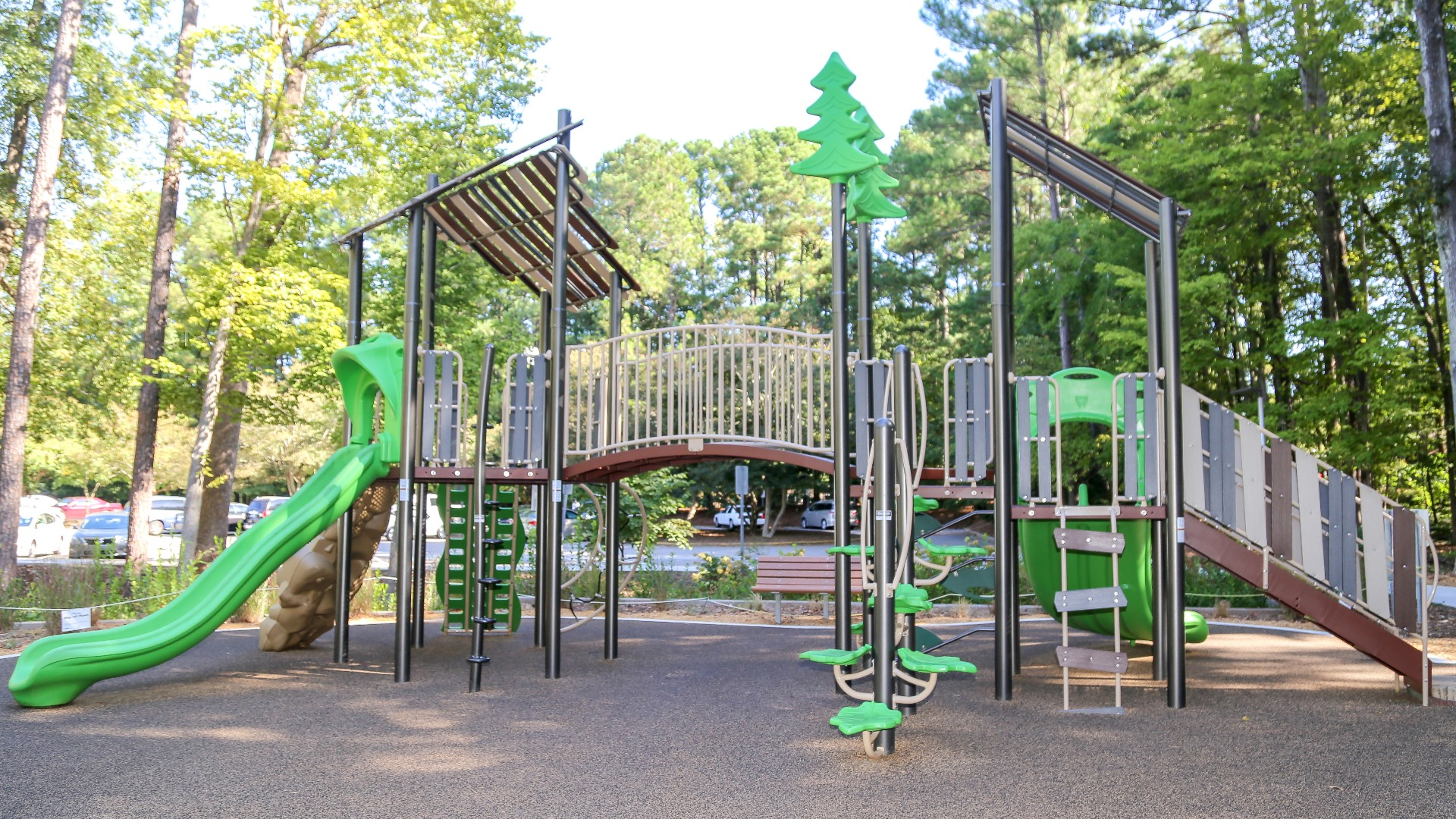 A large outdoor playground with climbing rocks, a slide, swings and more.