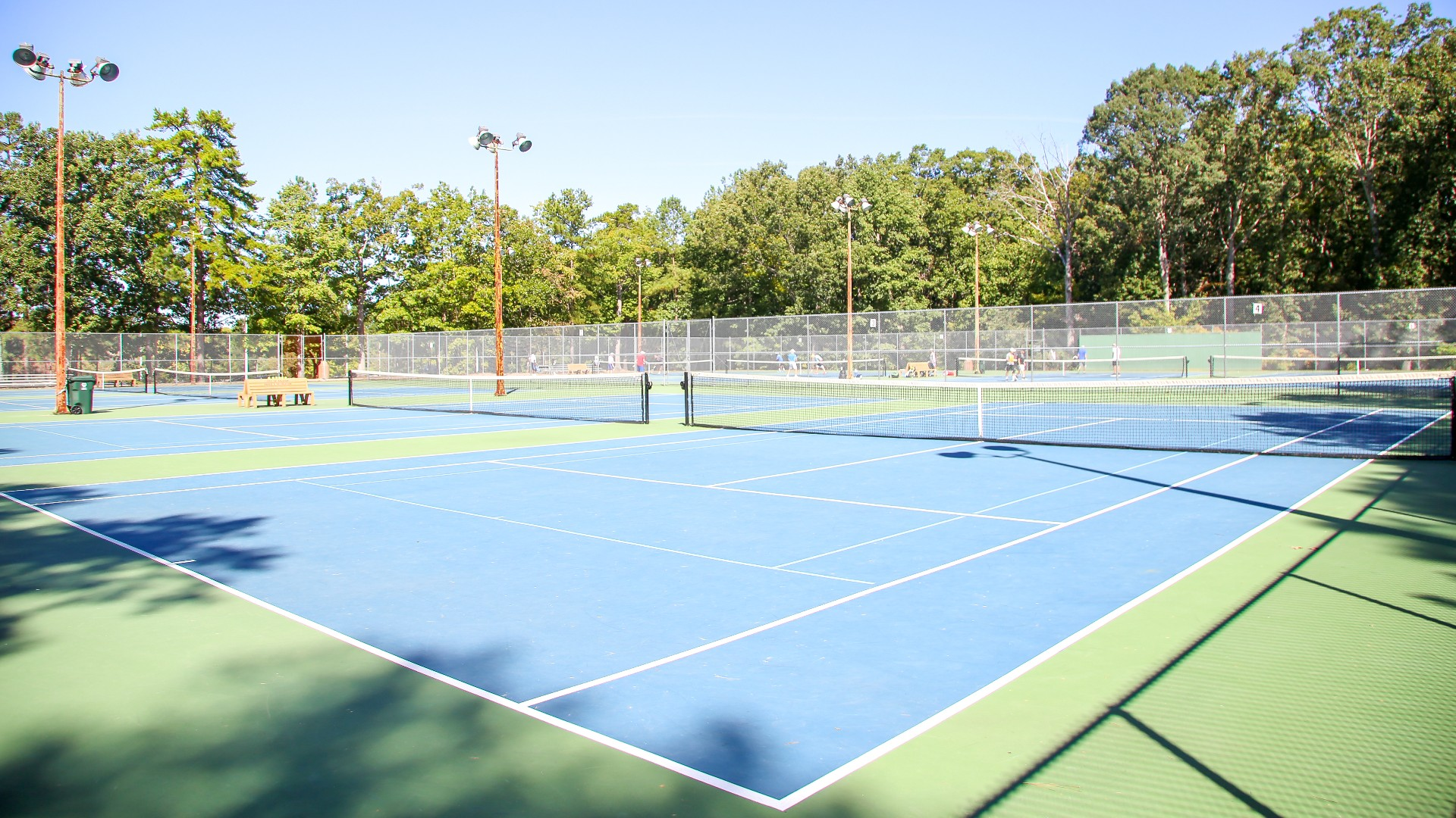 Shot of exterior tennis courts, eight total, at Optimist Park