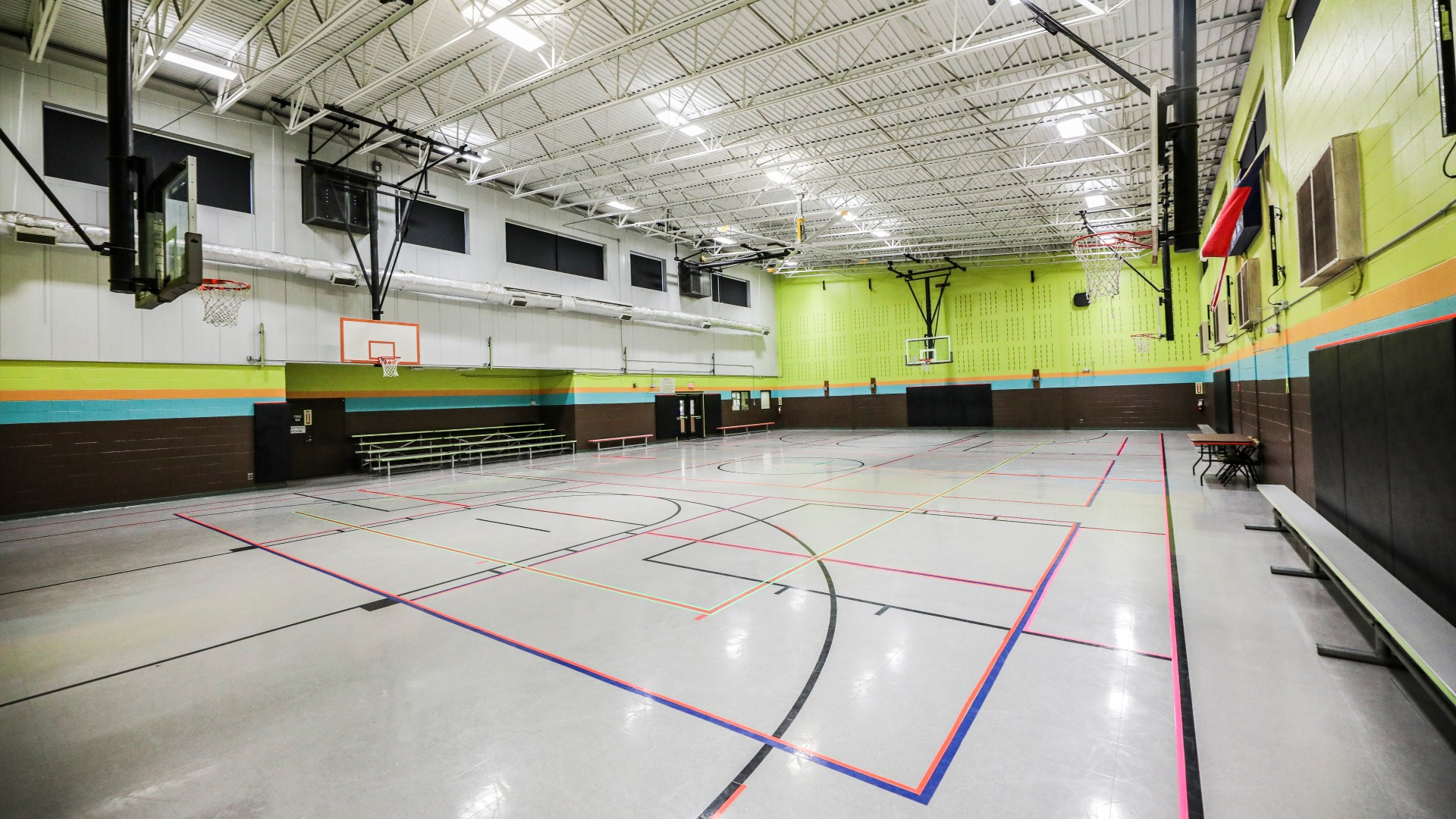 A large, brightly colored gymnasium with multiple courts