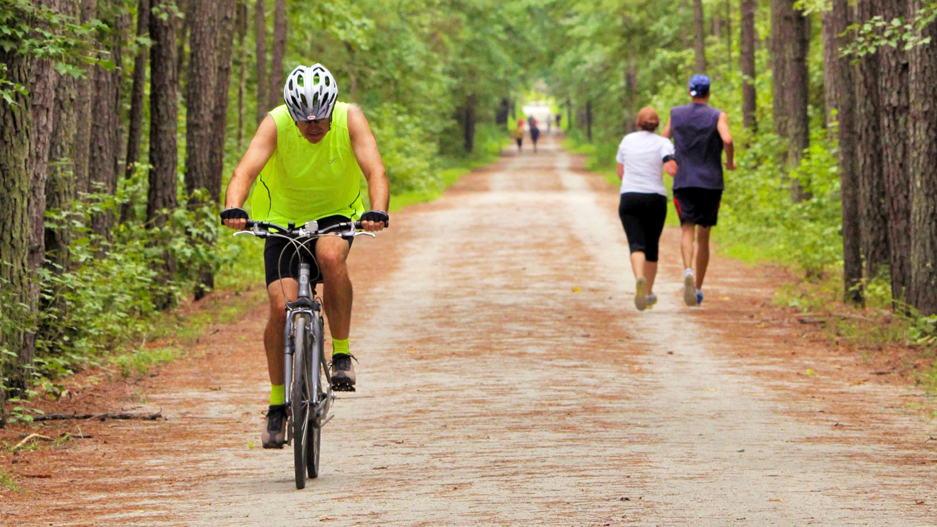 Man biking with two joggers on trail