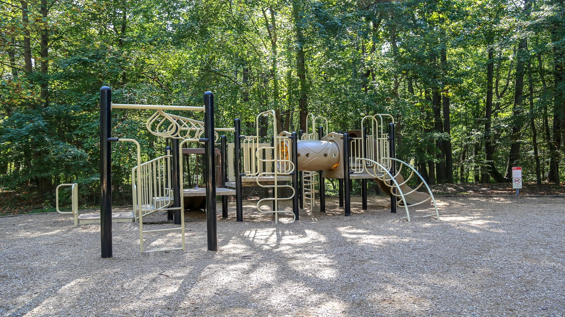 An outdoor large open playground with slides and monkey bars