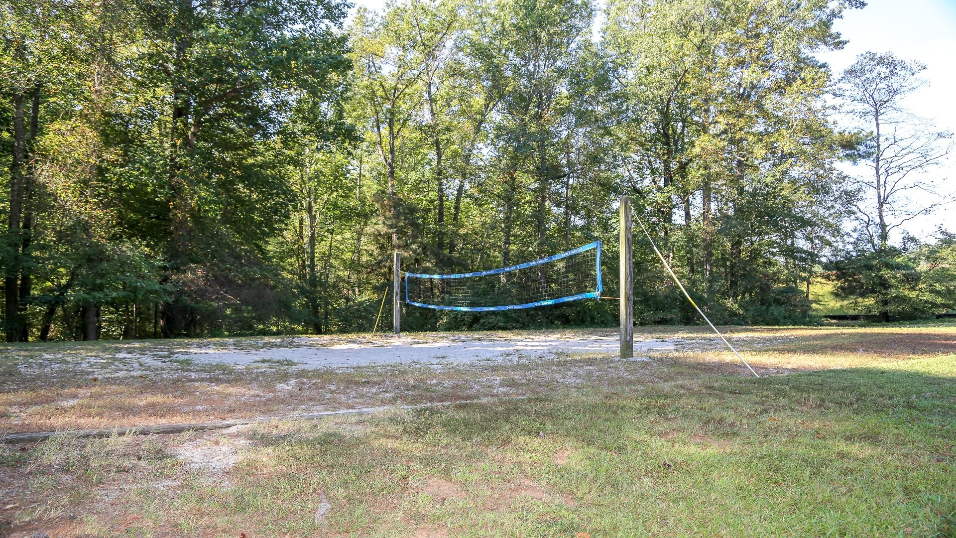 An outdoor sand volleyball court with one net