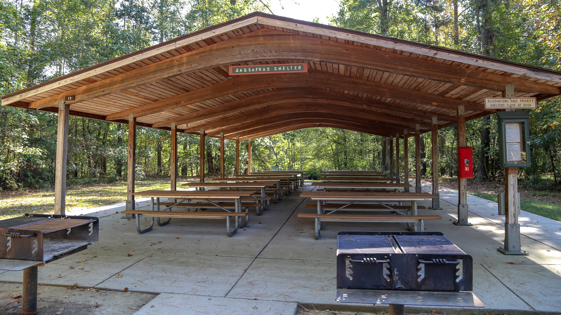 A large outdoor picnic shelter with grills