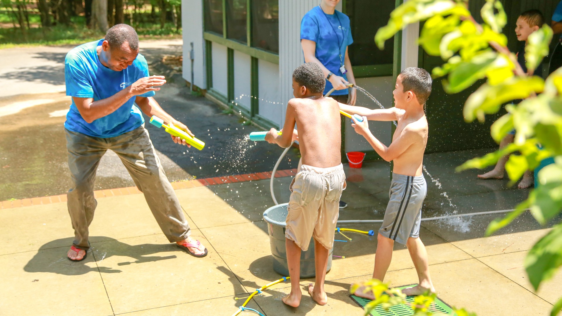 Kids playing with a water hose during a summer camp