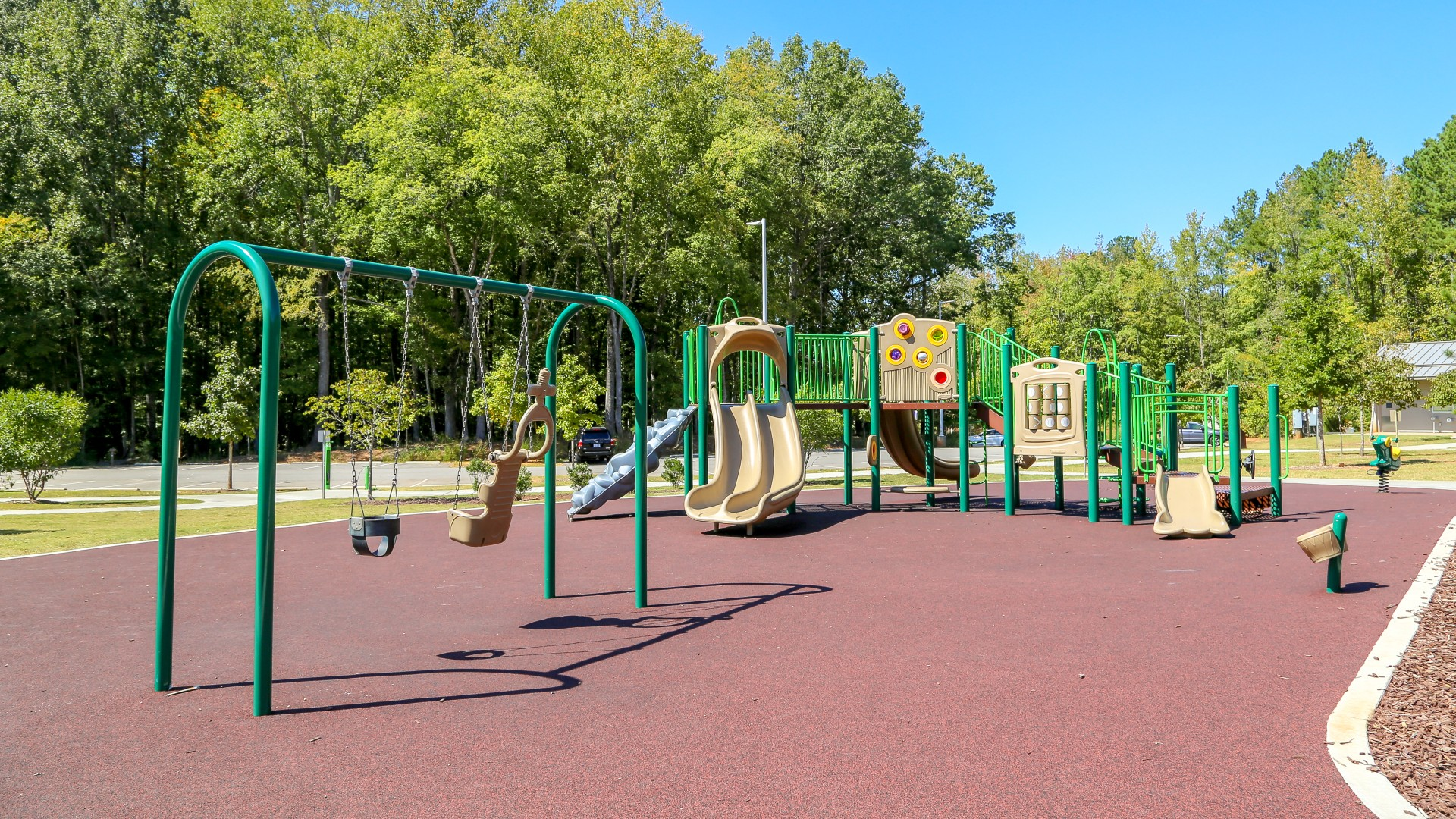 Part of the playground which includes zipline, slides, swings, climbing elements with rubber surfacing.