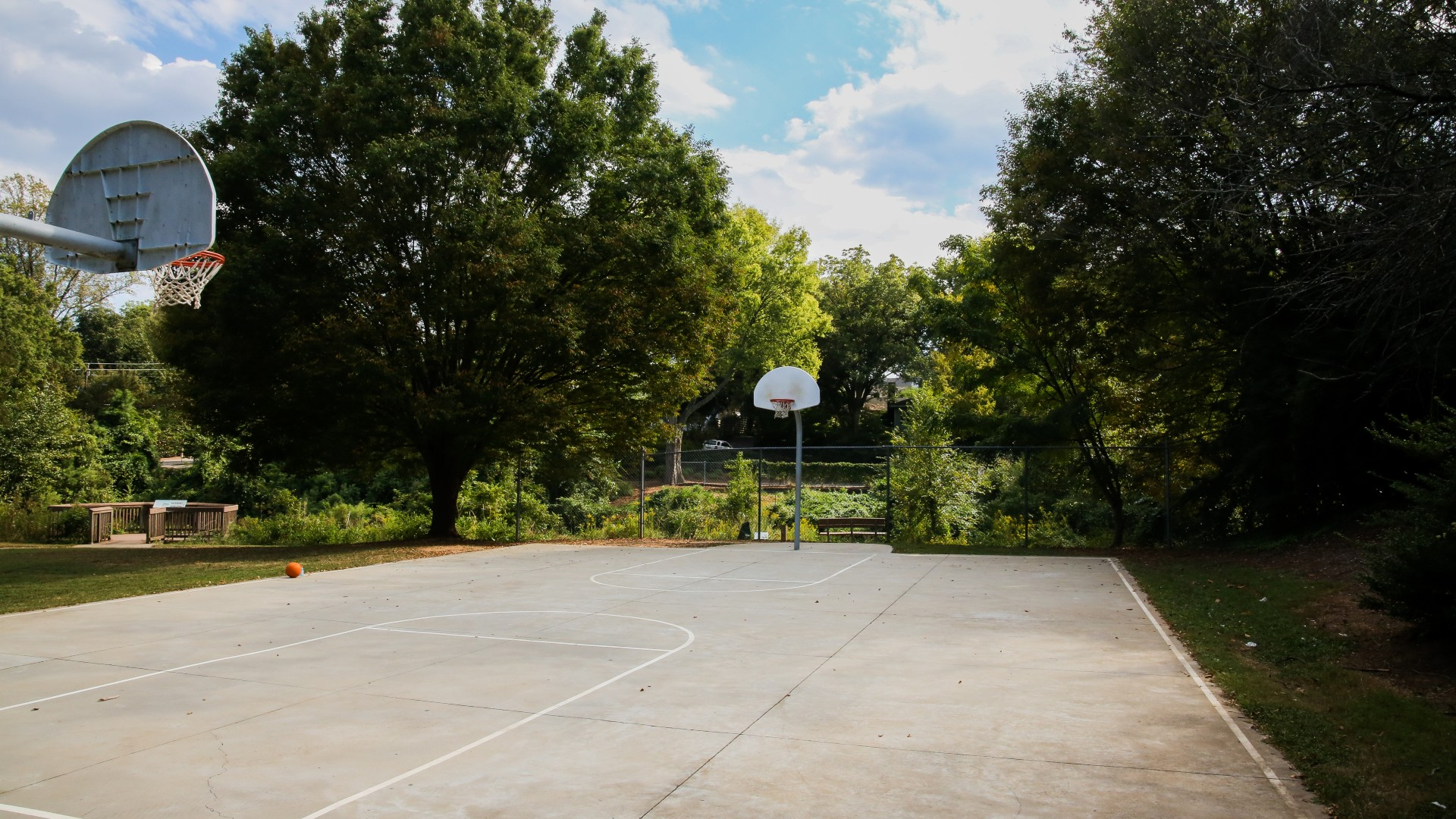 A concrete outdoor basketball court with two hoops