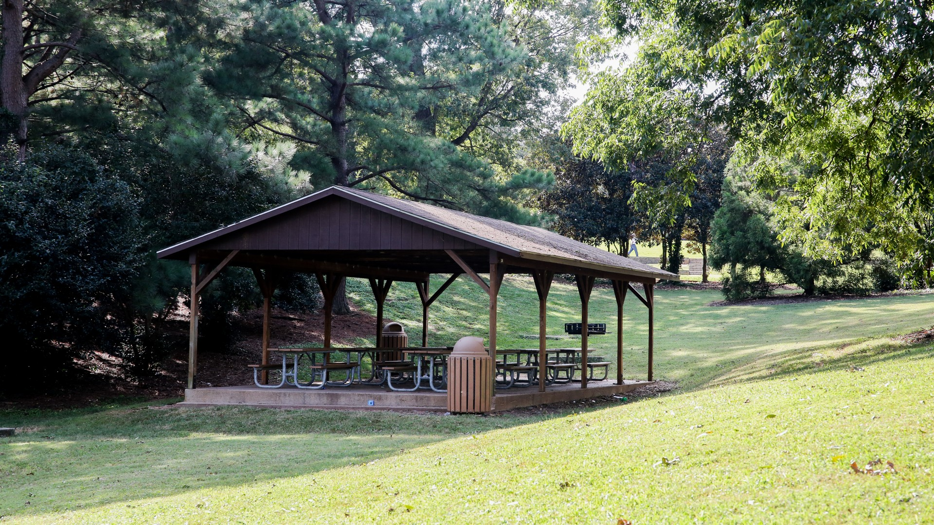 A large outdoor picnic shelter with eight tables
