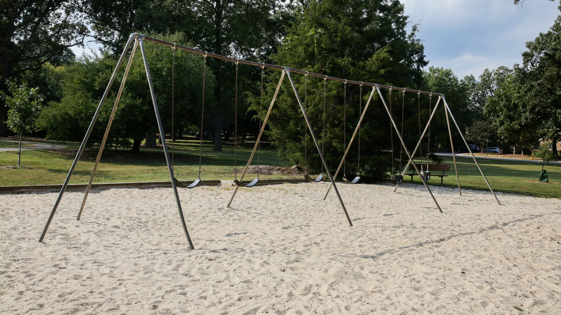 Several swings on a sand surface