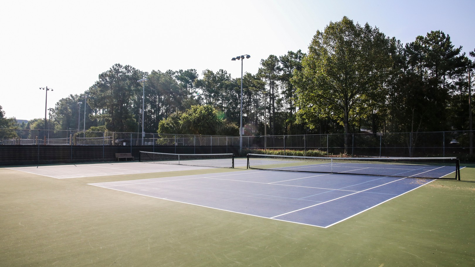 Two outdoor tennis courts with nets