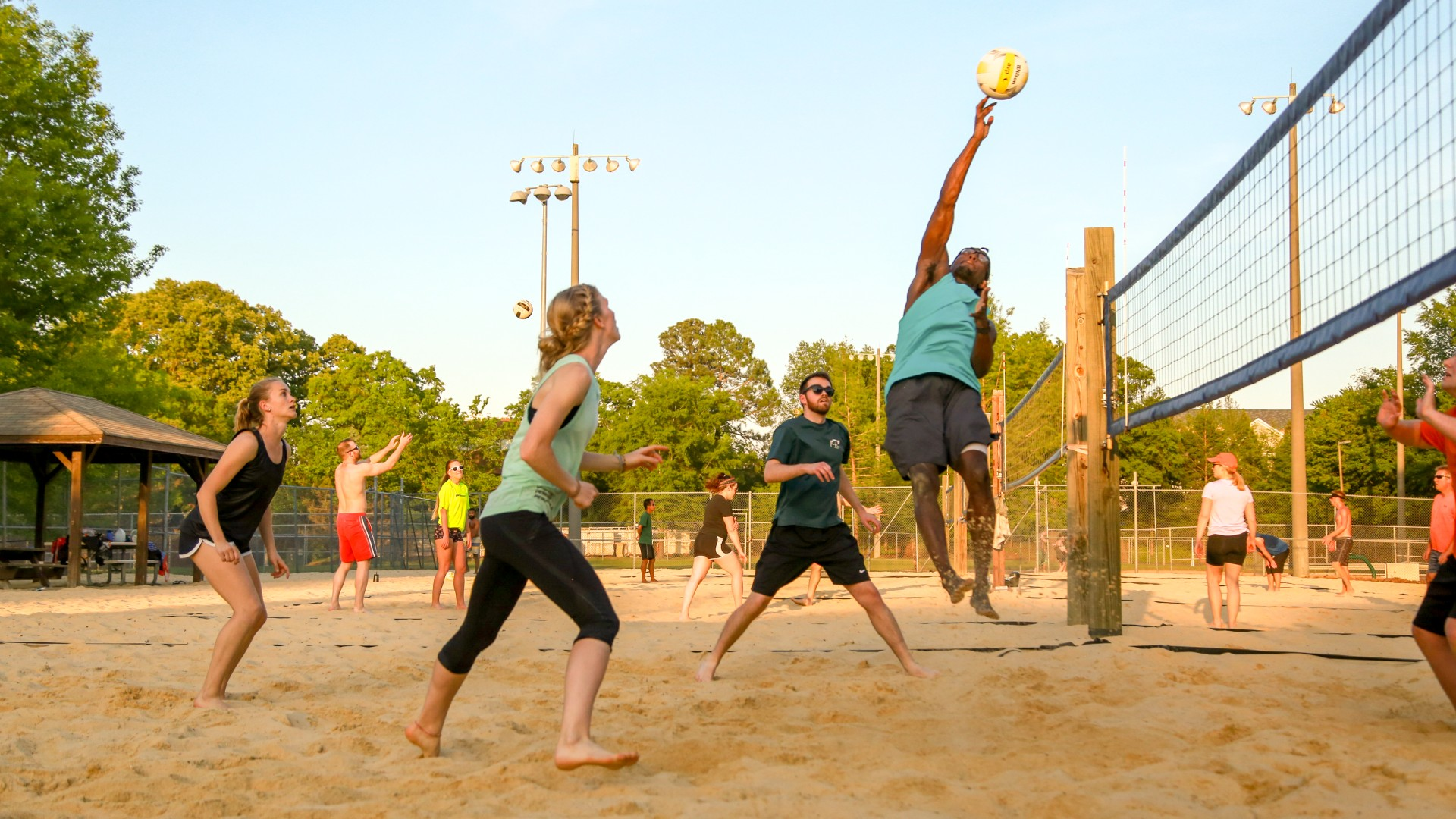 A group of young adults playing sand volleyball at Jaycee Park