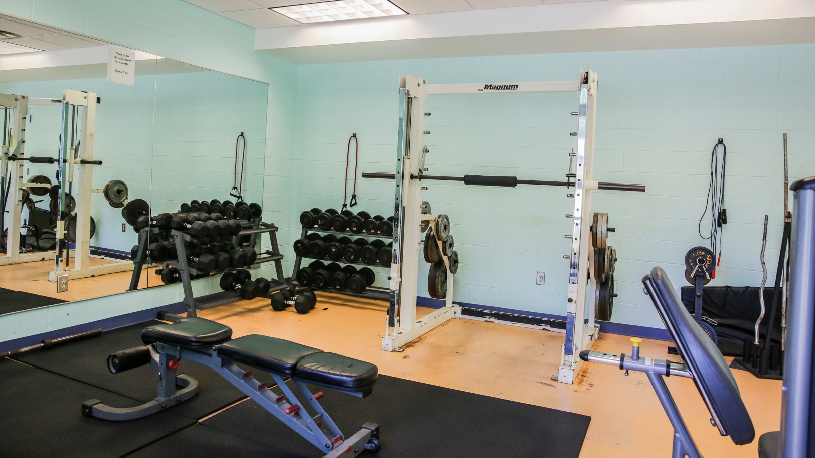 A weight room with free weights and workout equipment
