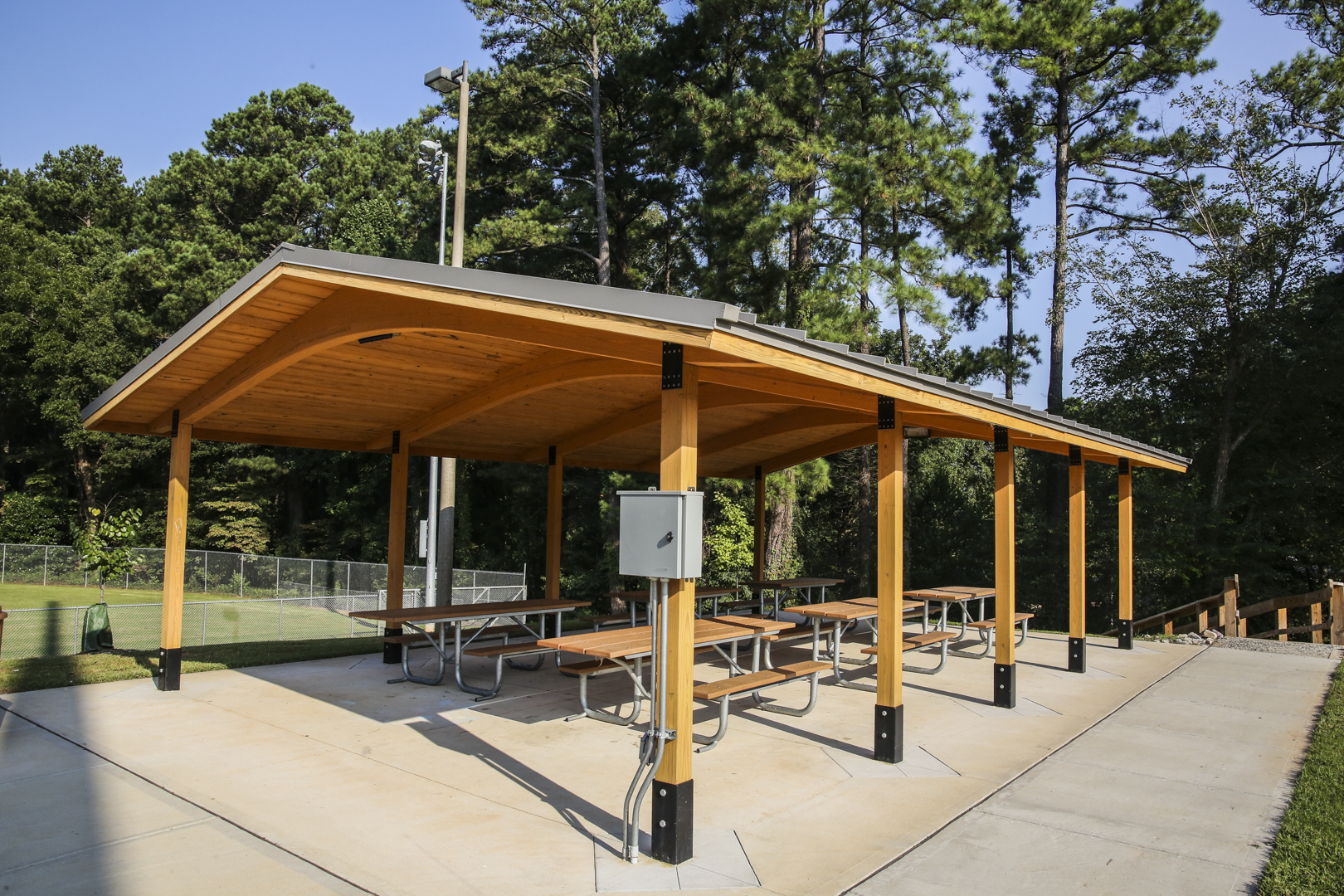 An outdoor covered picnic shelter with multiple tables