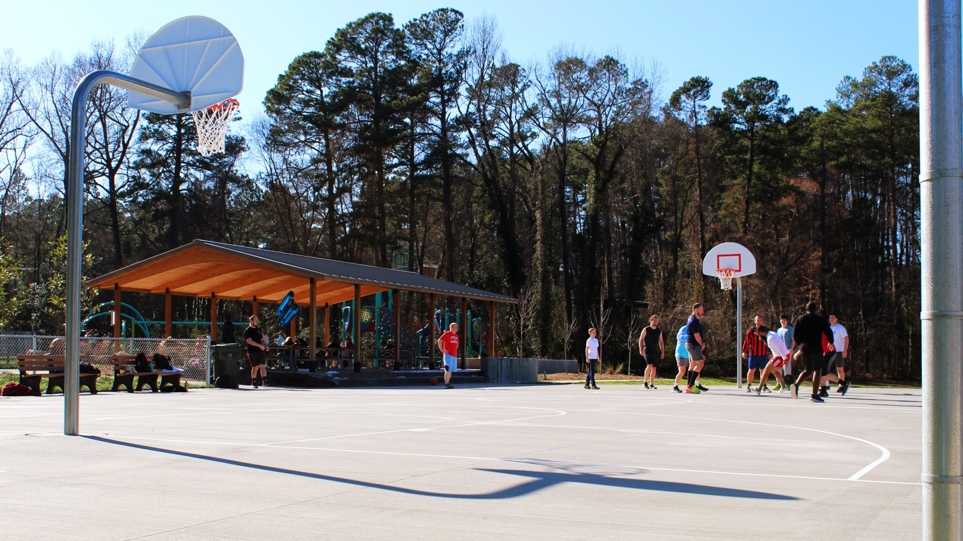 An outdoor basketball court with a concrete surface