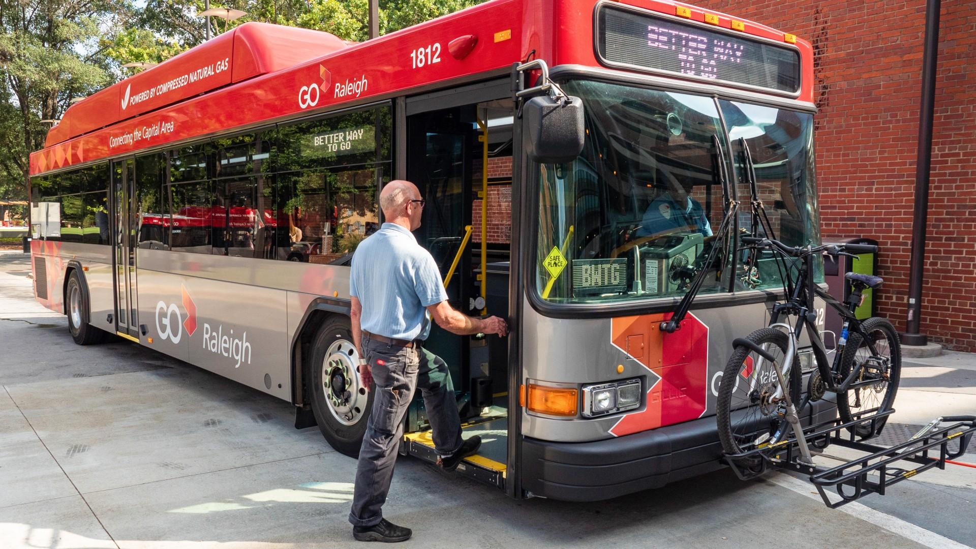 Man boarding bus after bike loaded on bus rack