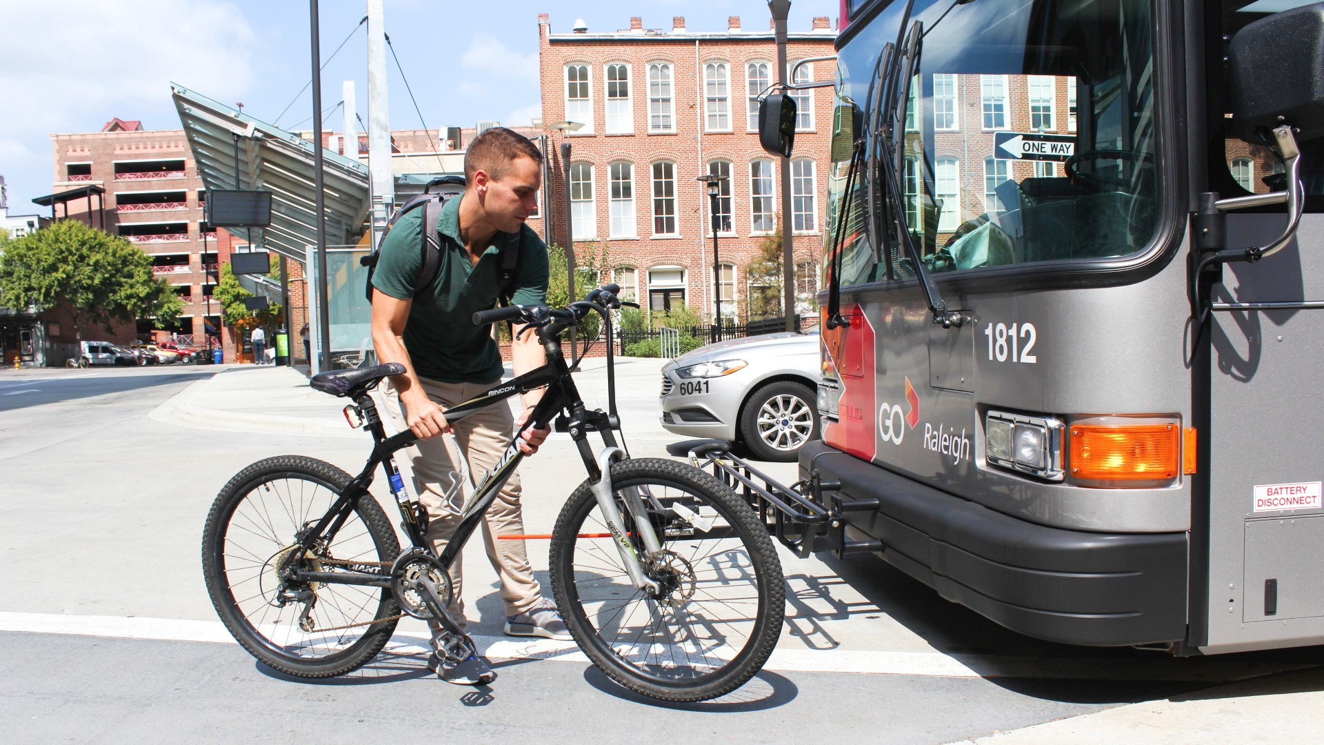 Man getting ready to load bike on bus rack