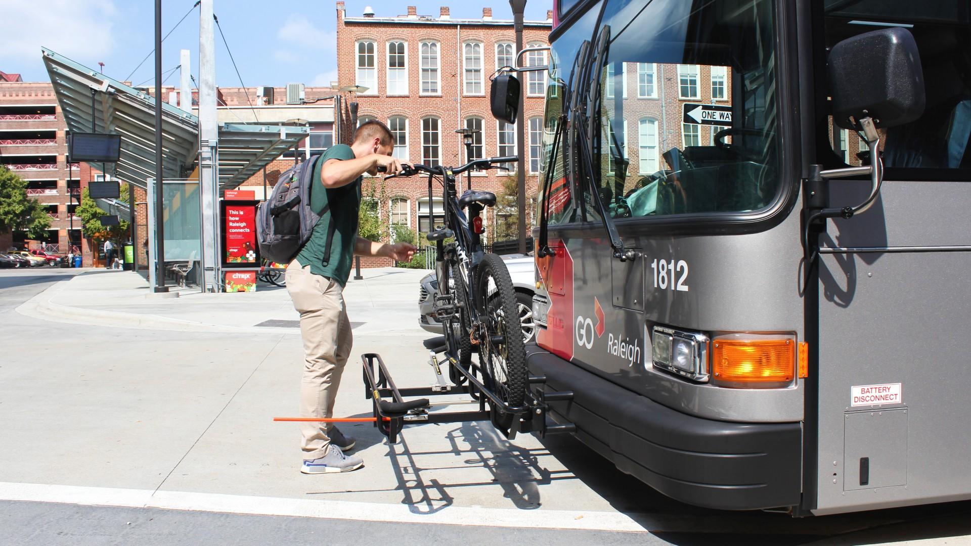 man loading bike on bus rack