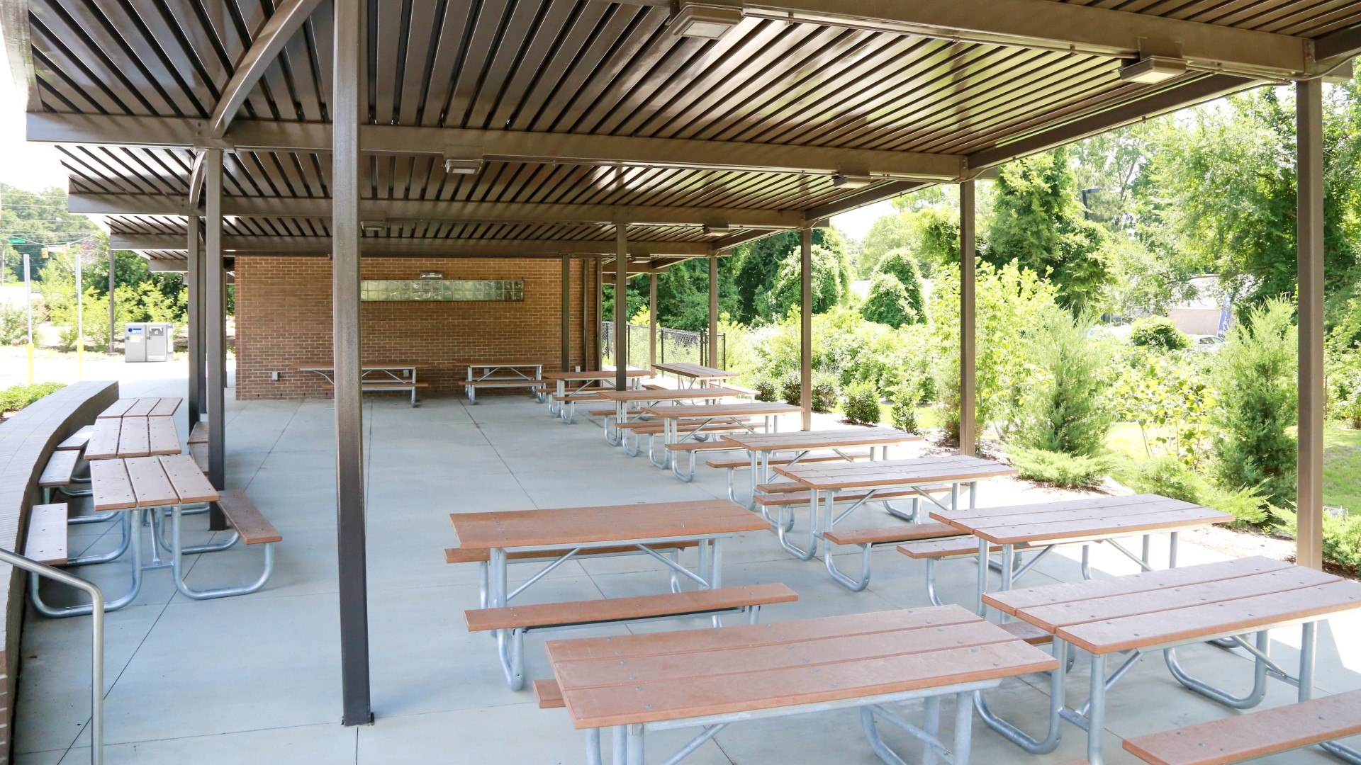 A large, open outdoor picnic shelter with over a dozen tables