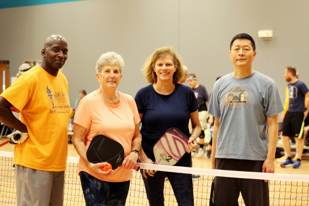 A group of adults playing pickleball