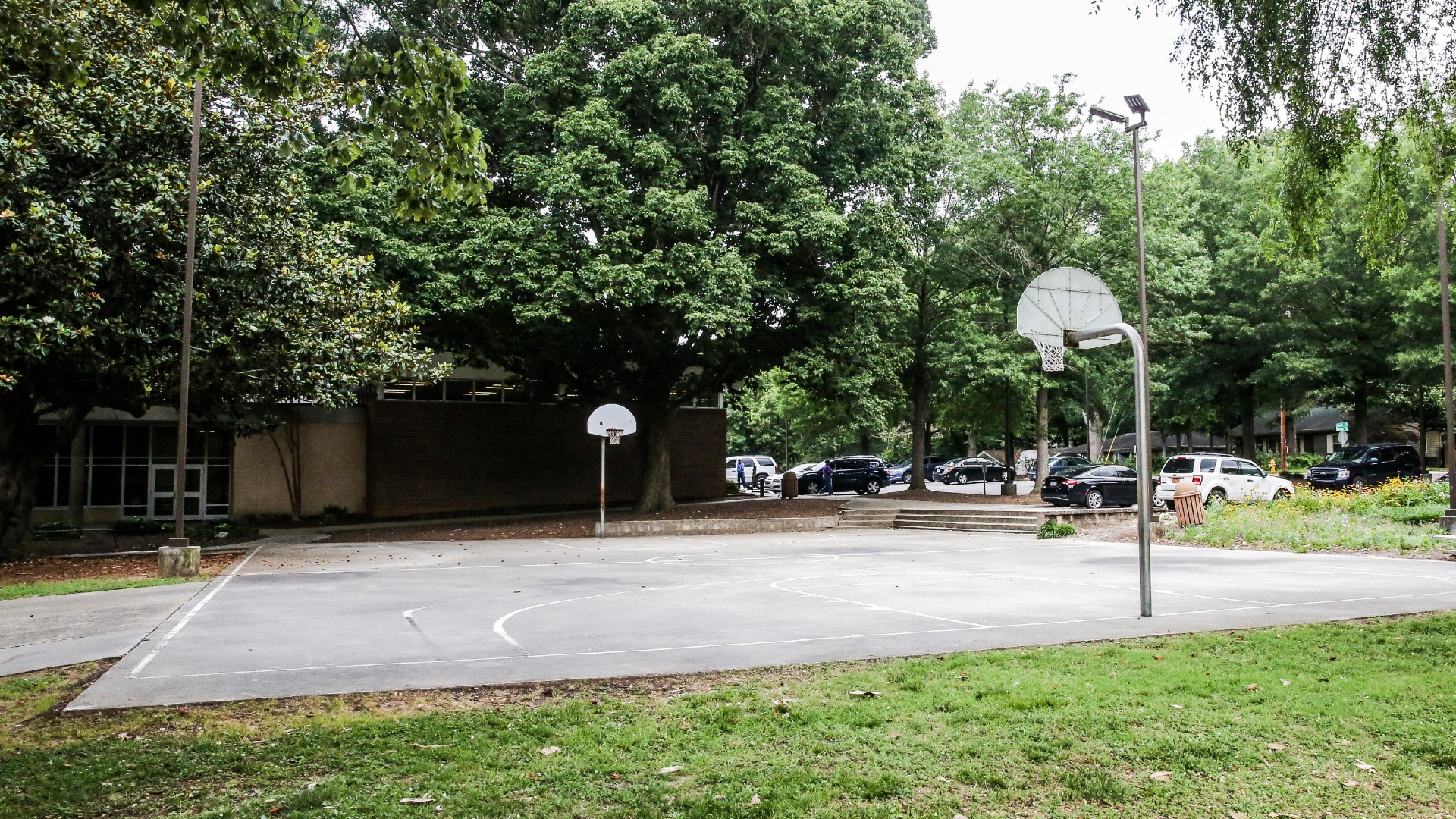 An outdoor basketball court with concrete surface