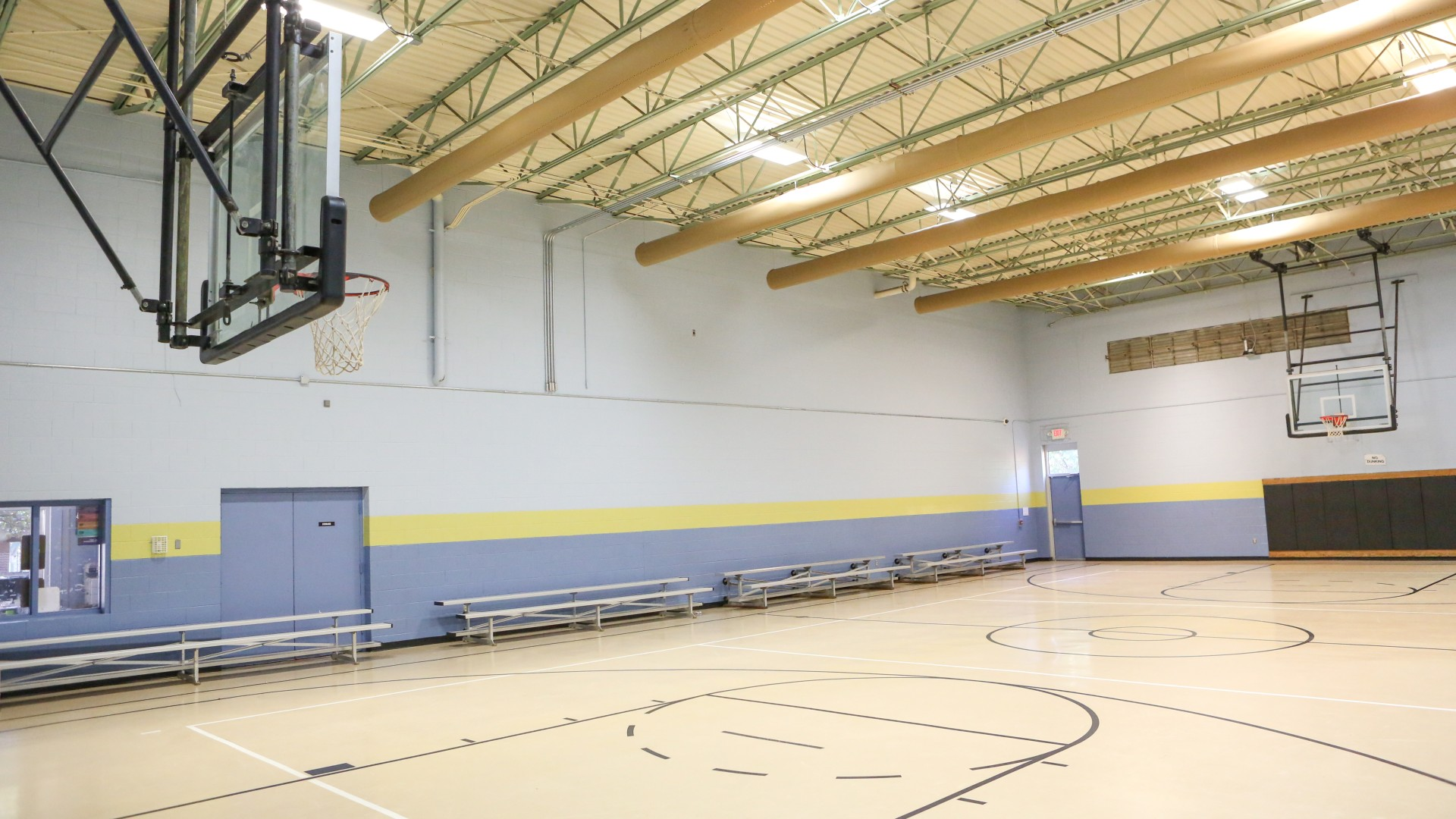 An indoor gymnasium with basketball court