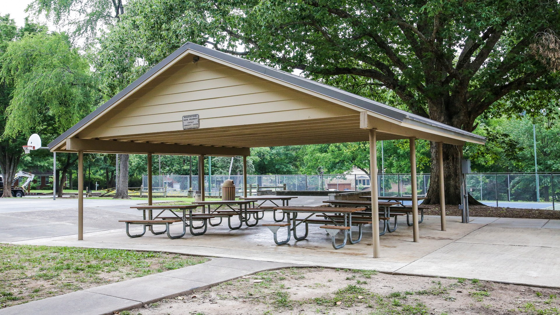 A large outdoor picnic shelter with six tables