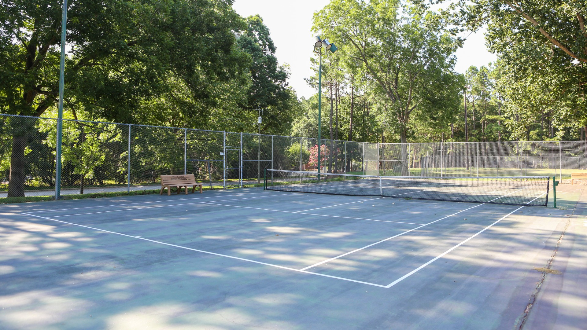 Two outdoor tennis courts with backboards and lighting